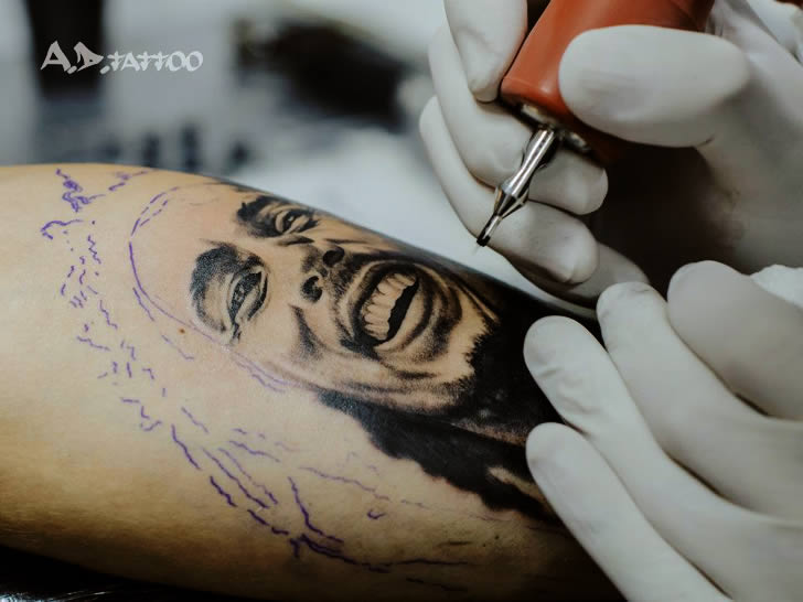 AD Pancho tattooing a Bob Marley picture on client