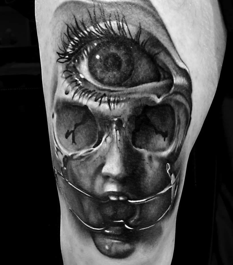 Scary doll face with big eye. Tattoo by Nick Chaboya