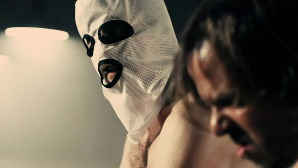 "The mysteriously masked man and Milos (Srdjan Torovic) in ""A Serbian Film"" (2010)."