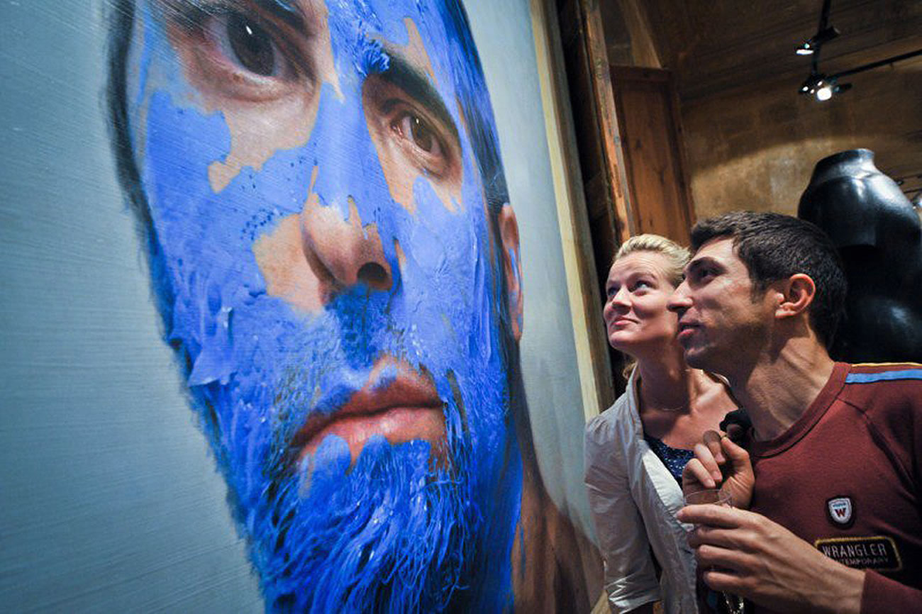 man with blue paint on face by Eloy Morales