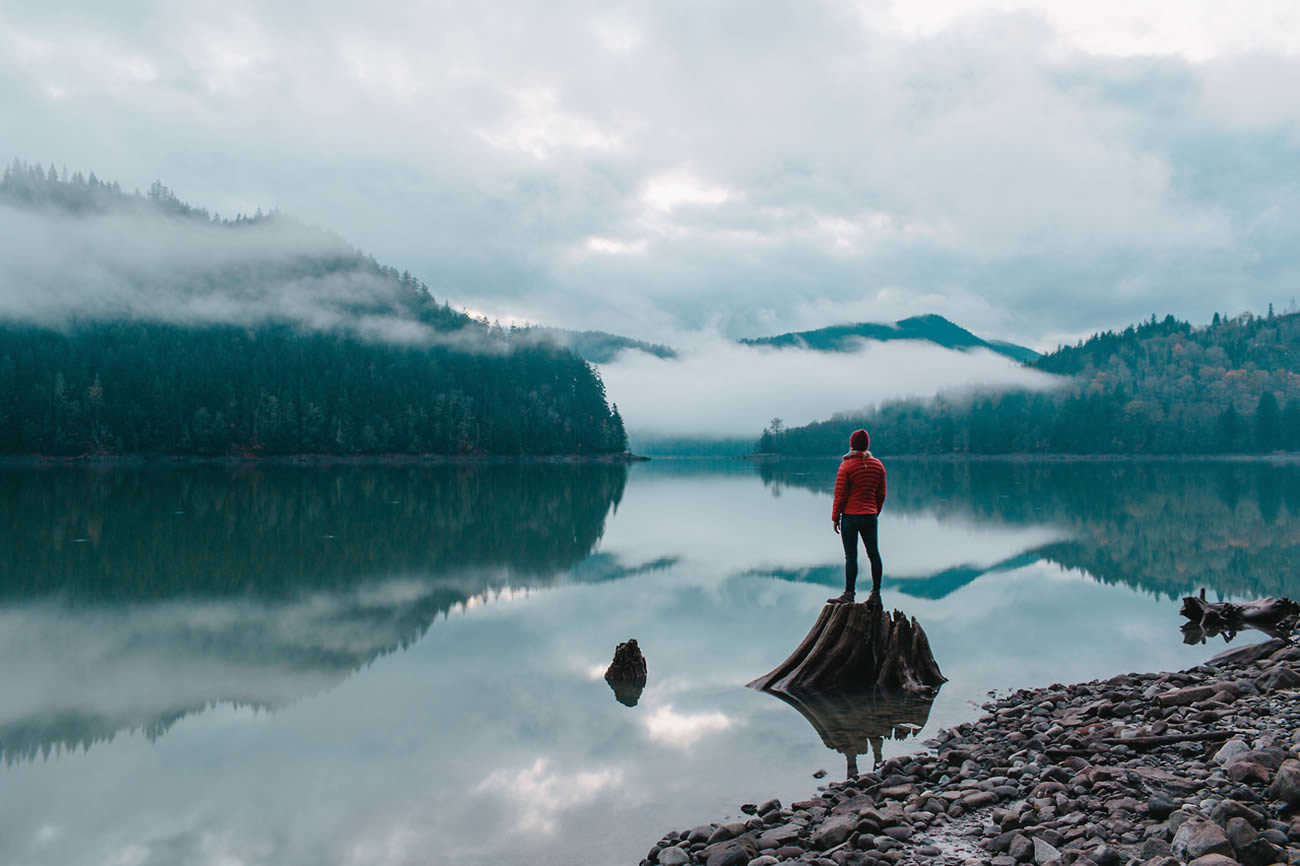 man in red jacket looking out on lake by jared chambers