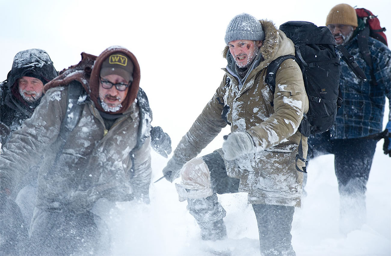 they grey, liam neeson and men cross snow path