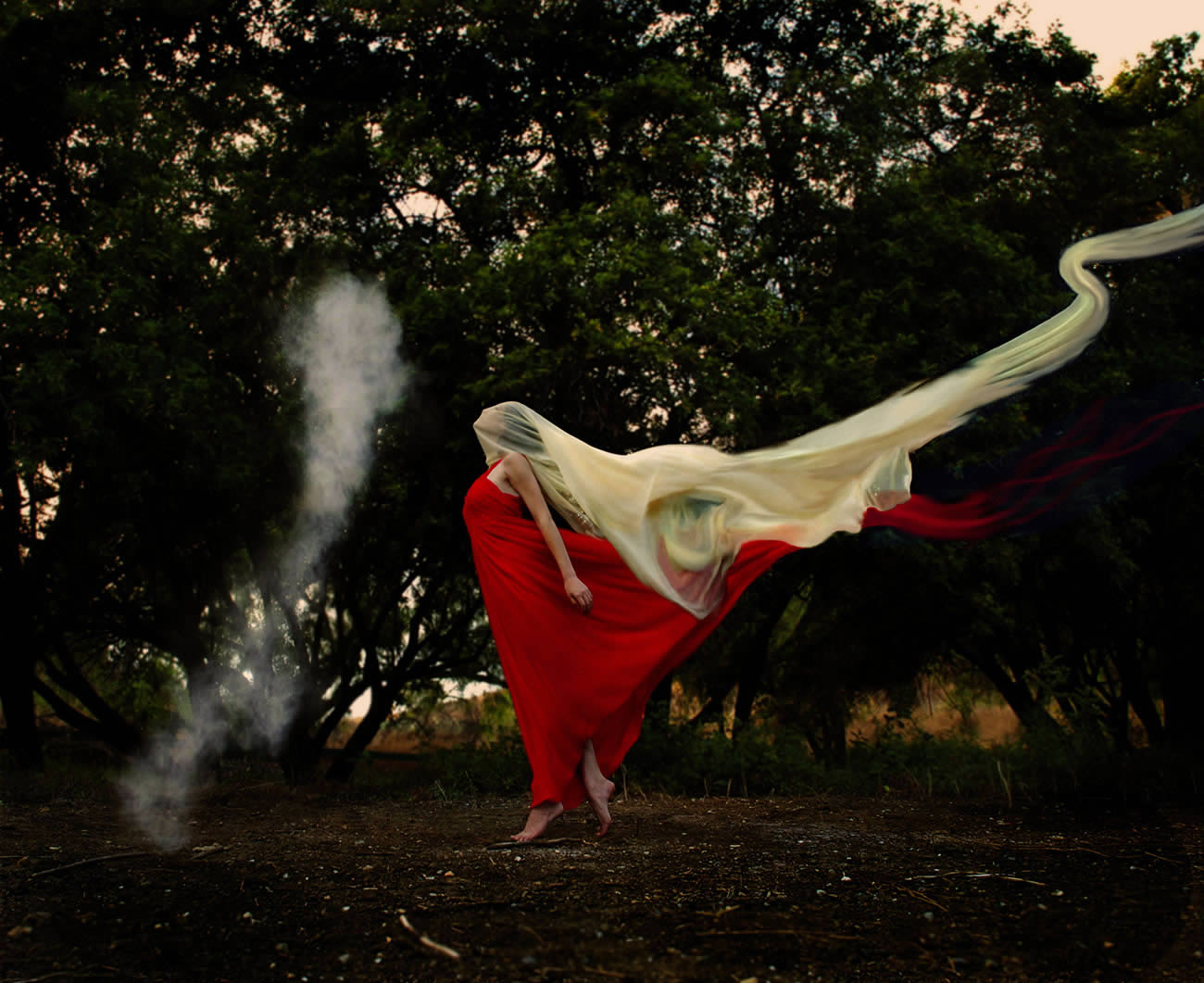white cloth on hand and red dress, photography by trini schultz