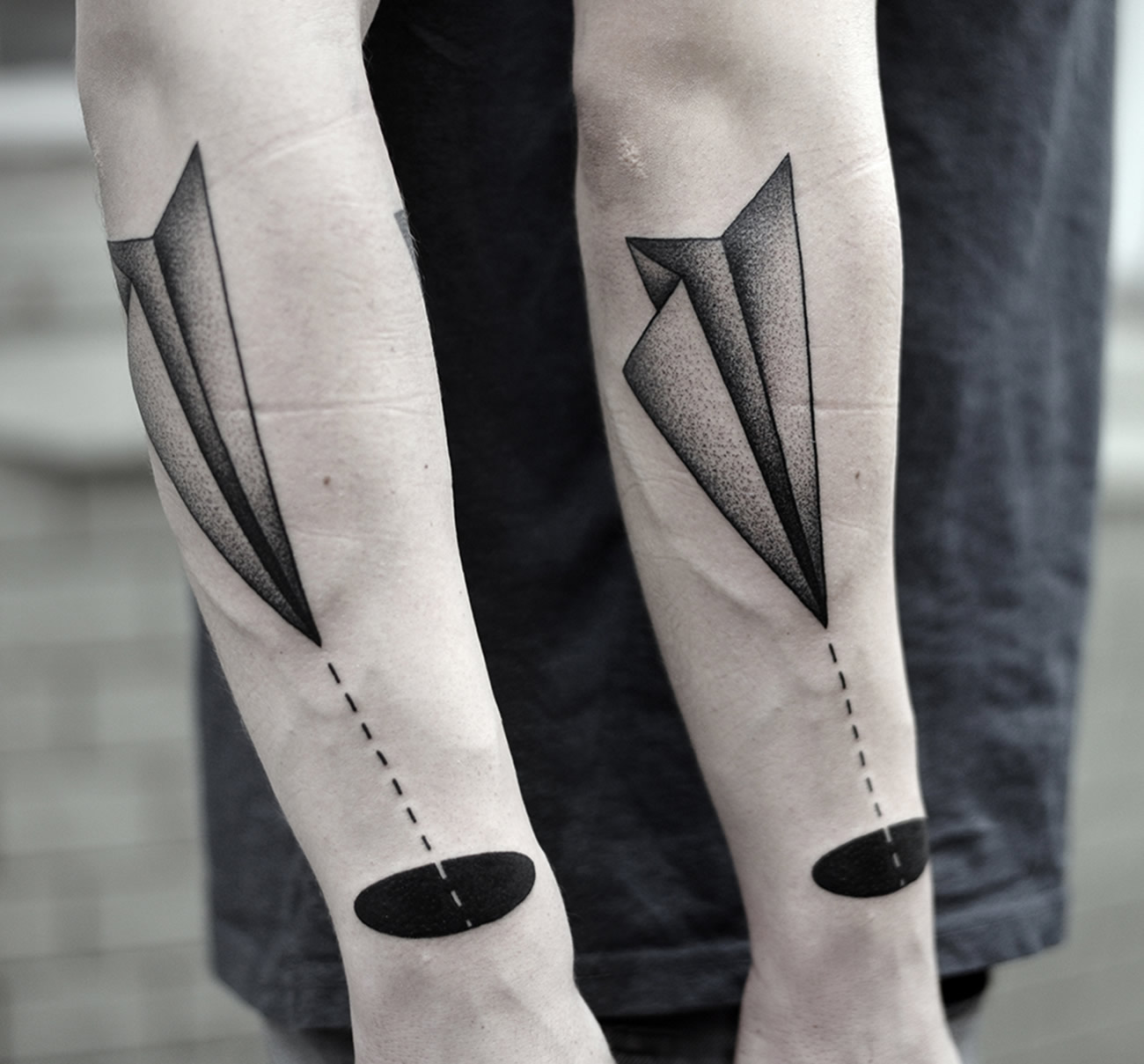 paper plane flying into black hole, tattoo by Kamil Czapiga