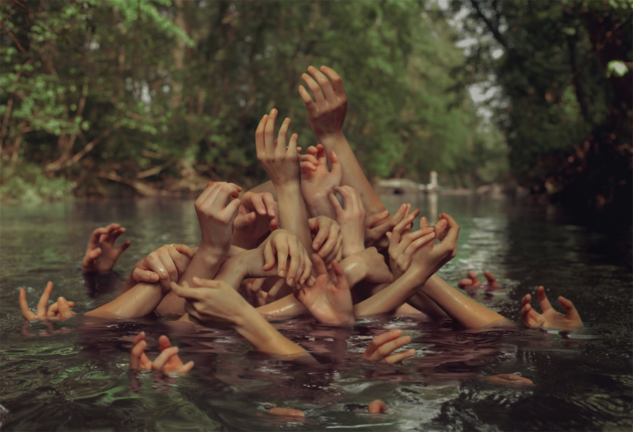 hands coming out of lake, photography by kyle thompson