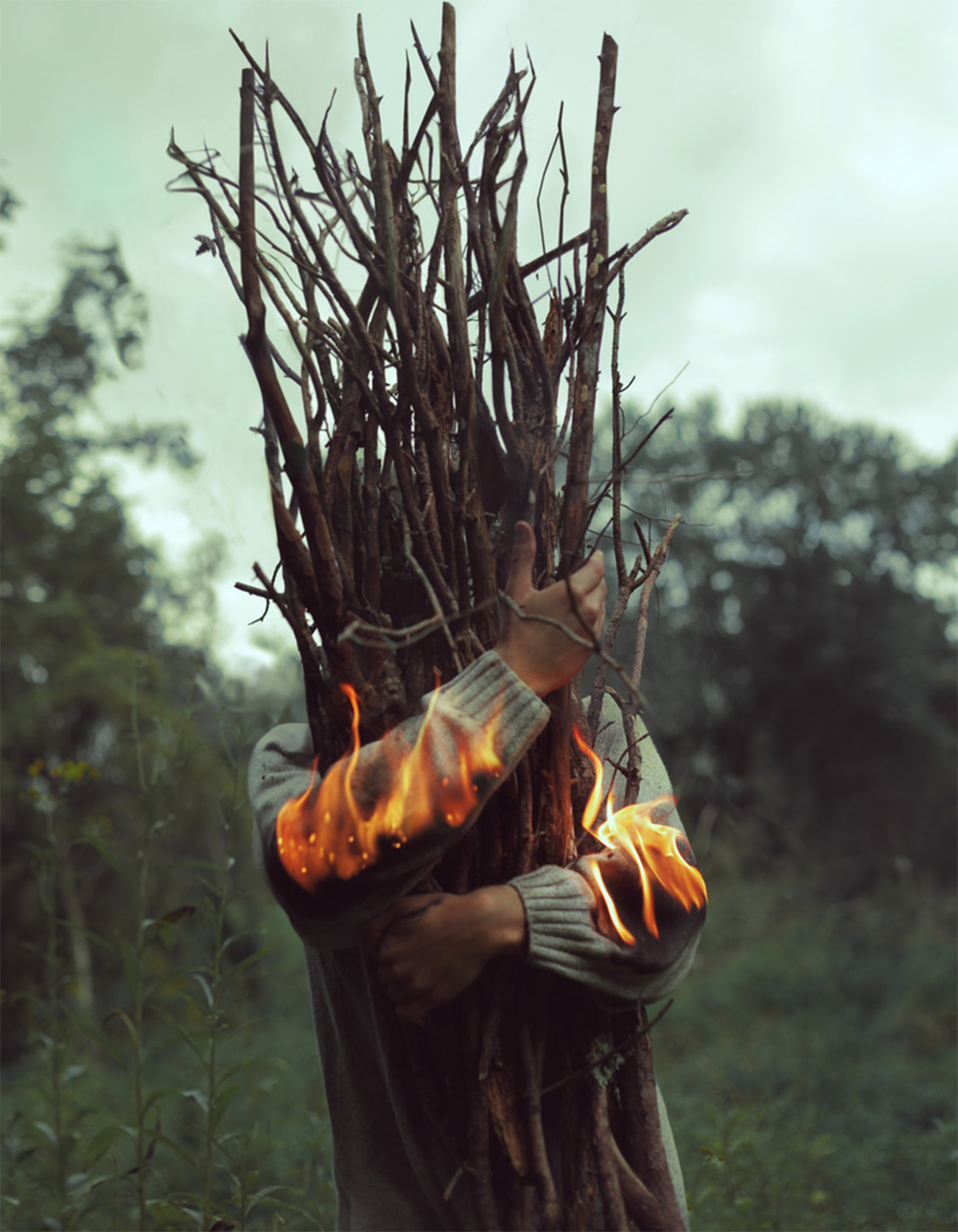 man holding branches with fire on arms, photography by kyle thompson