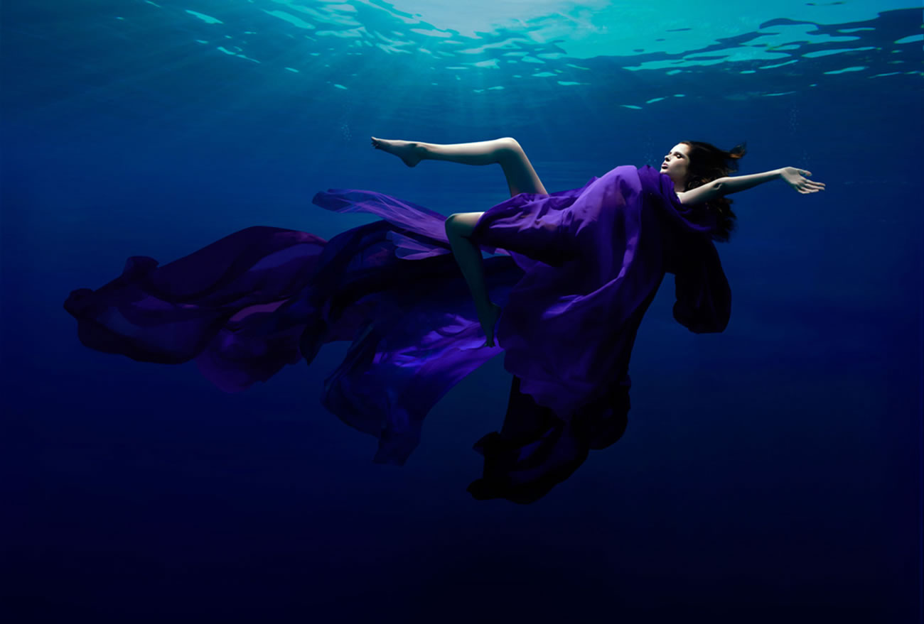 woman underwater, purple dress, photography by Patrick Curtet