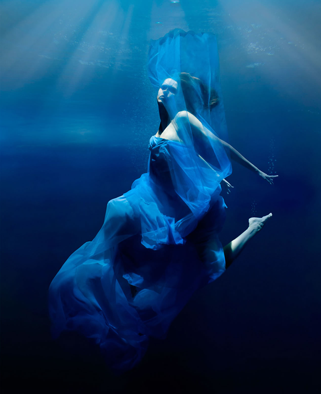 woman underwater, blue dress, photography by Patrick Curtet