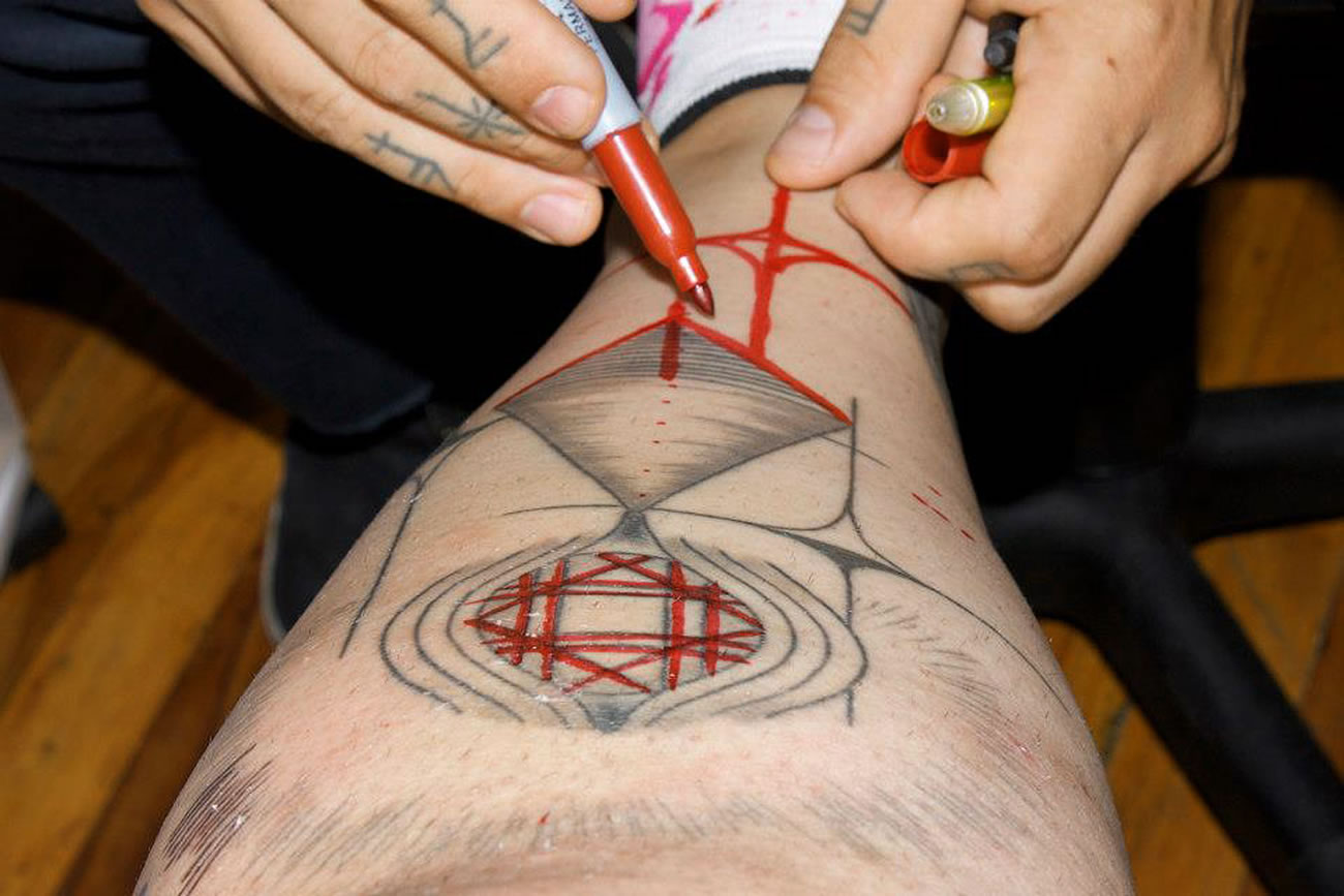 Brody Polinsky drawing on client's leg