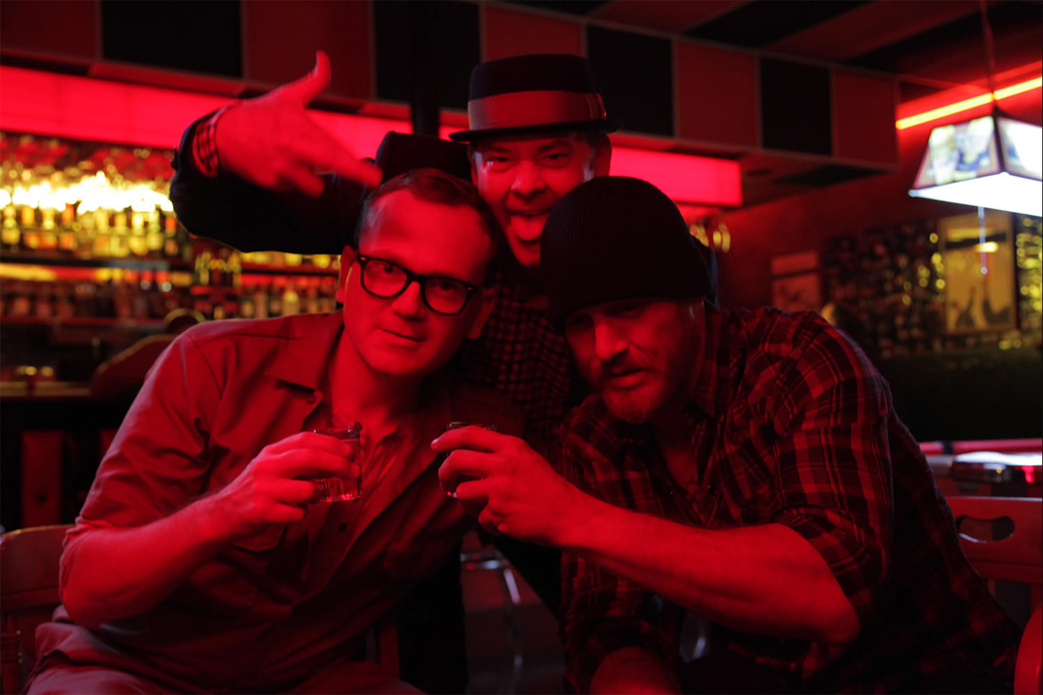 three guys at a bar, with red light, cheap thrills