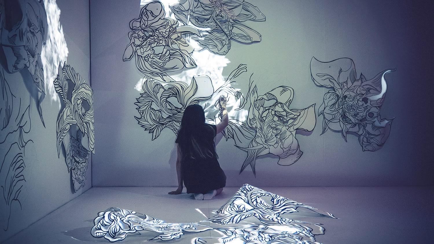 artist Sougwen Chung drawing on a wall
