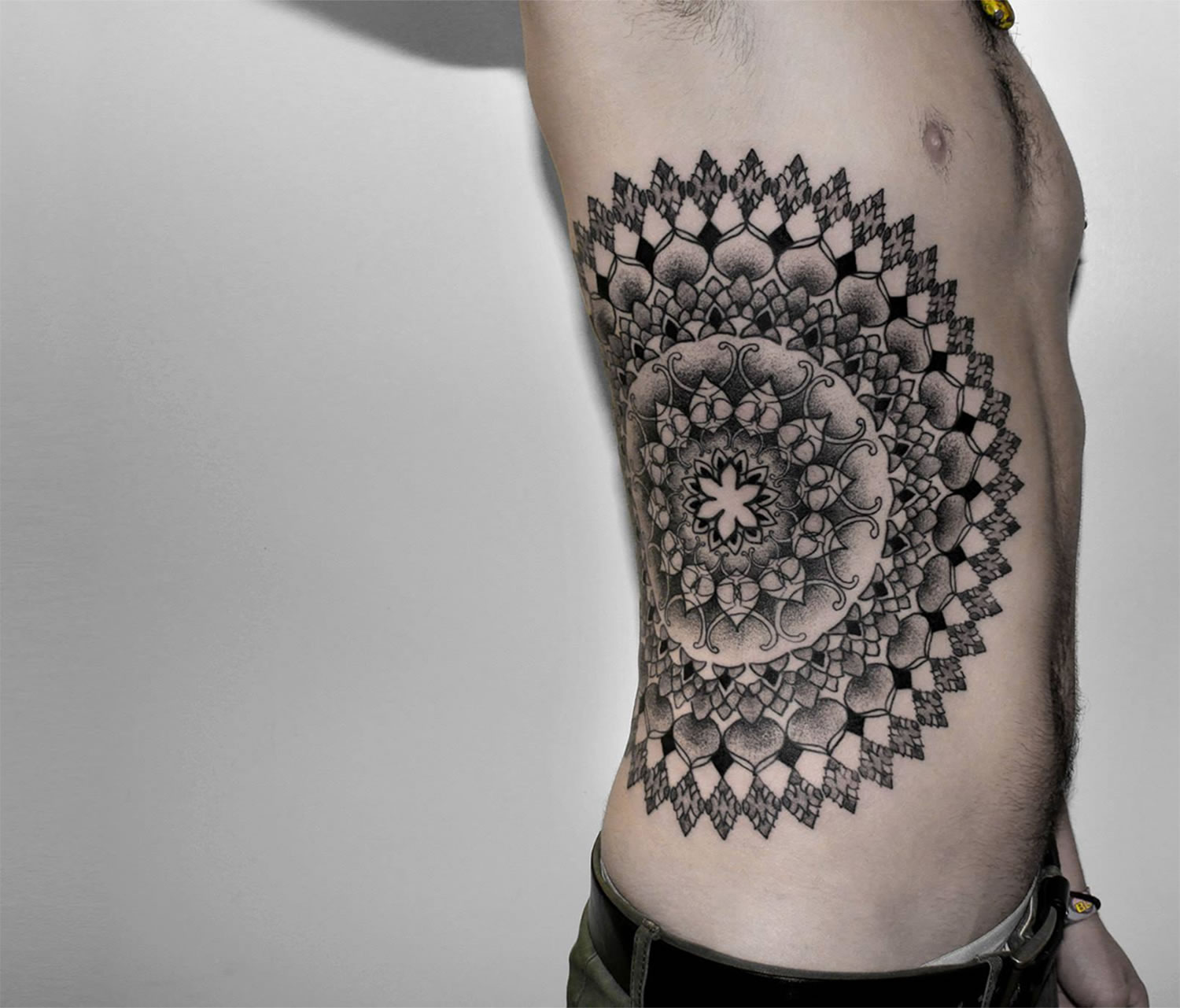 mandala tattoo on side of rib by chaim machlev