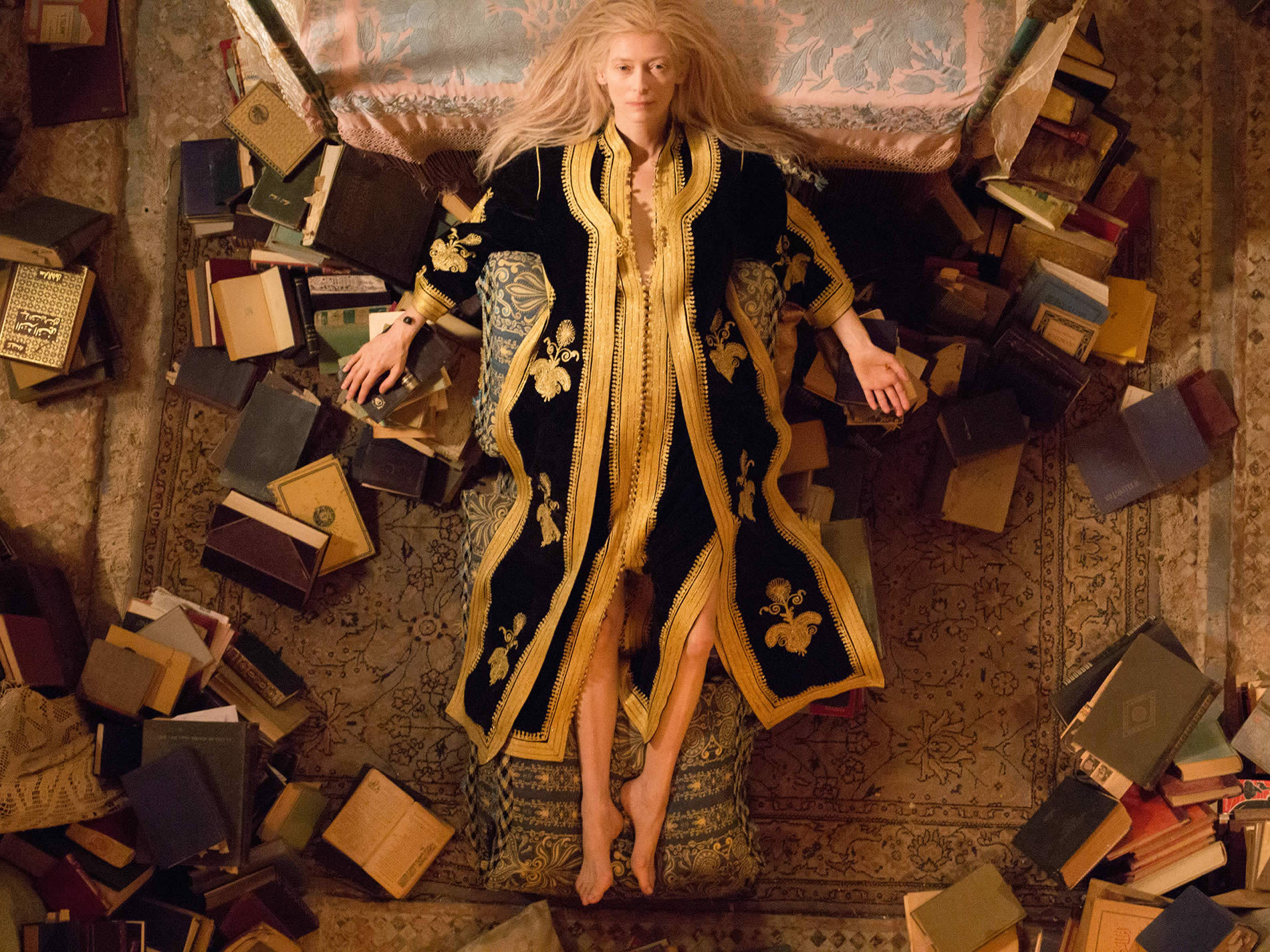 Tilda lying down with books all around, in the only lovers left alive