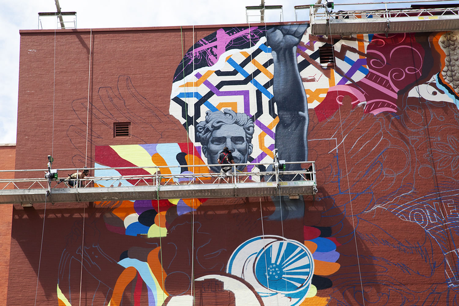 Tristan Eaton working on a mural, colorful art