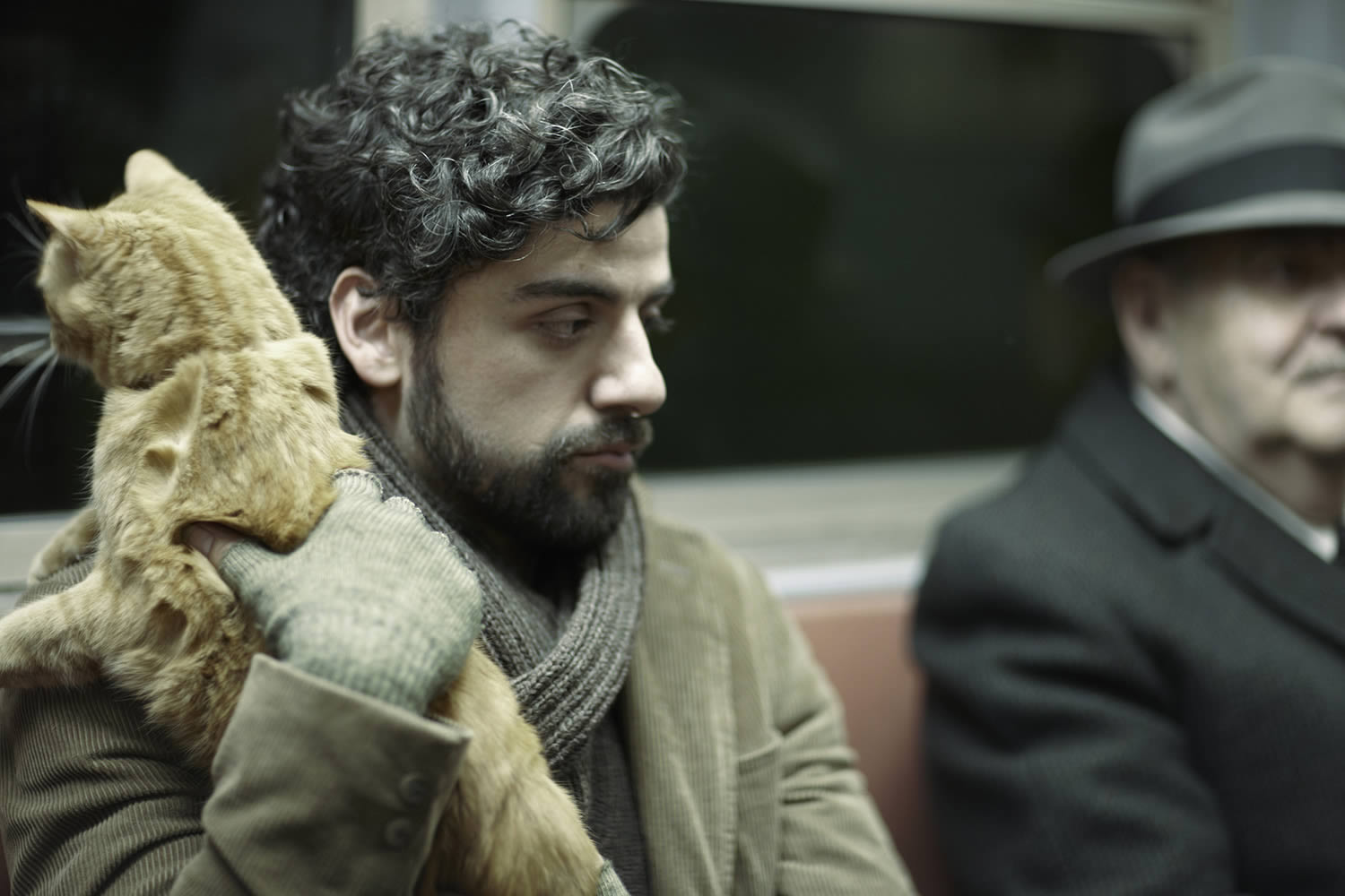 oscar holding cat in subway train. from Inside Llewyn Davis