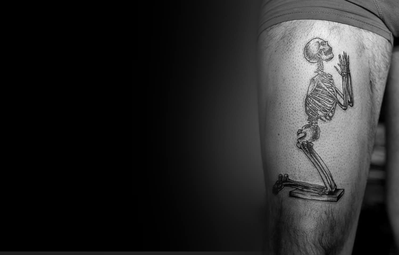 skeleton praying, tattoo by roman boyko