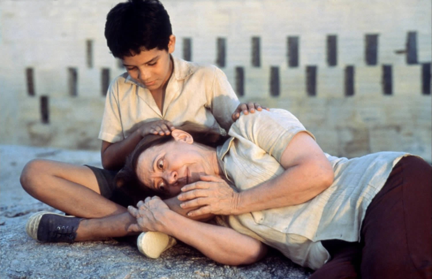 child embracing woman who is lying on the ground, in Central Station movie