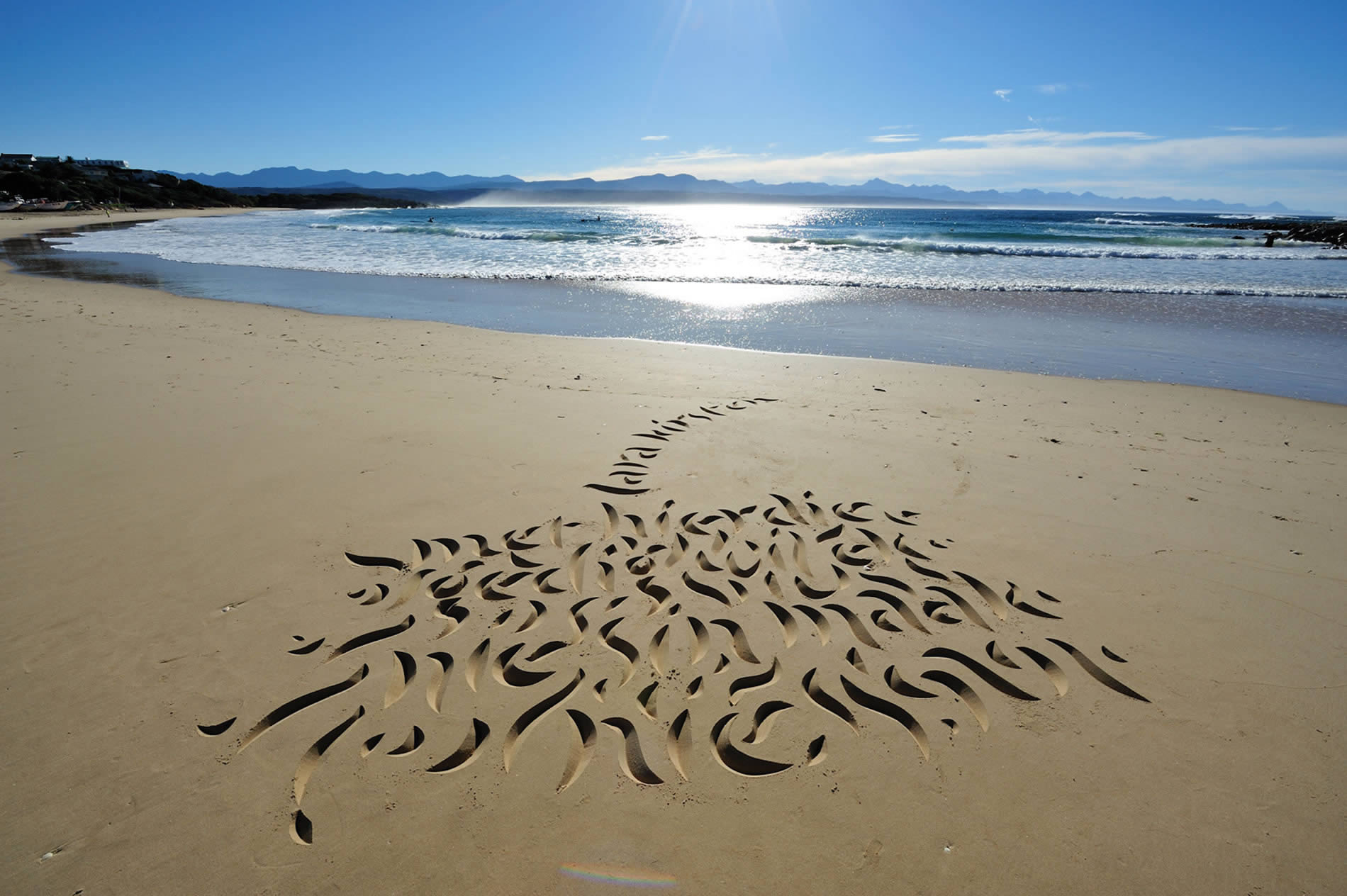 beautiful calligraphy on the beach, sunny day