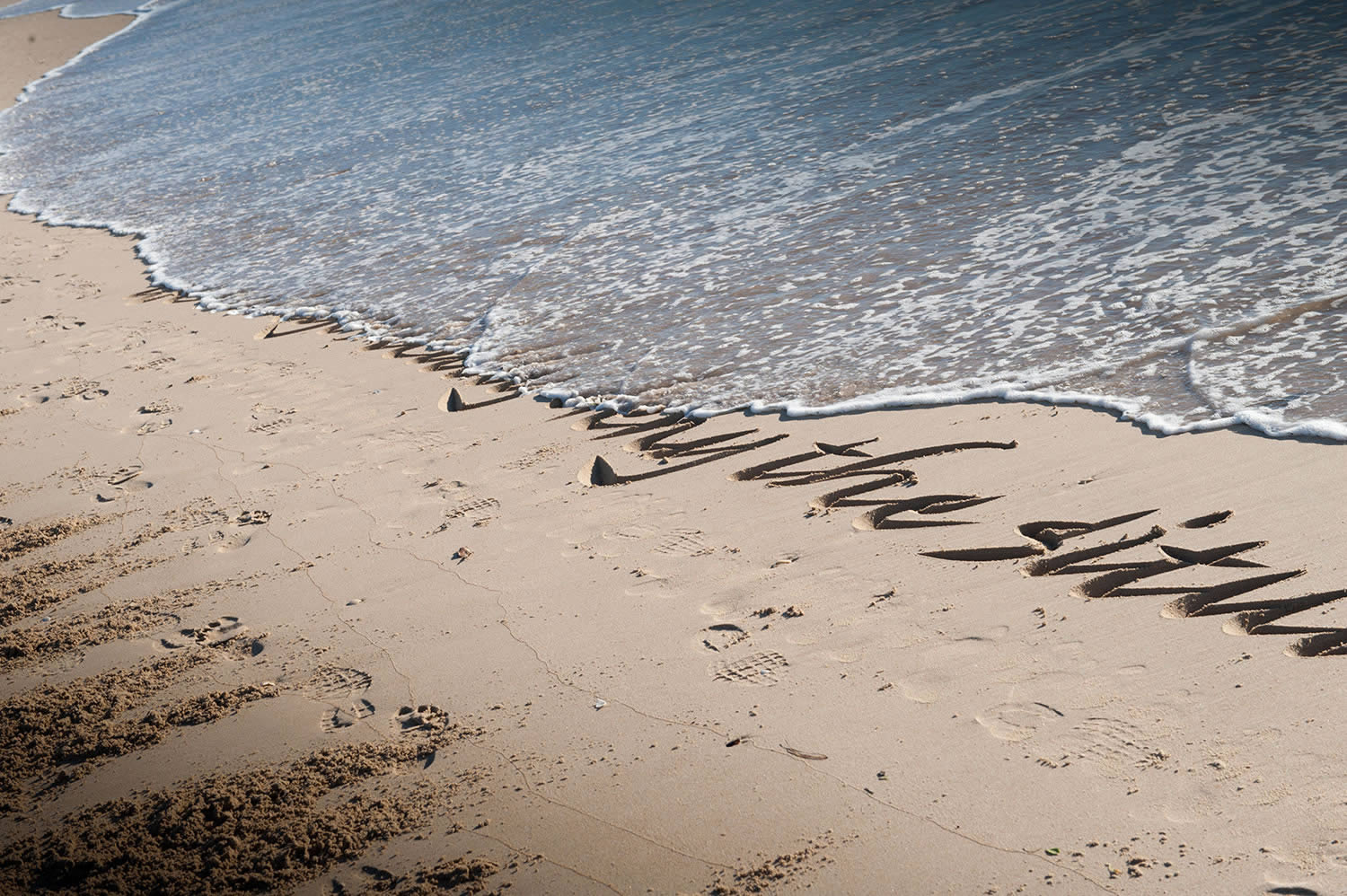 letters on sand washed away