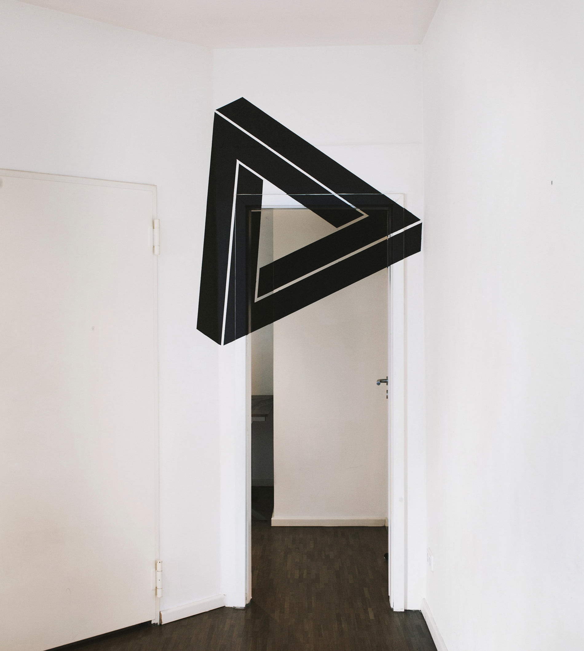 penrose triangle on white wall over door. Anamorphic art by fanette g.