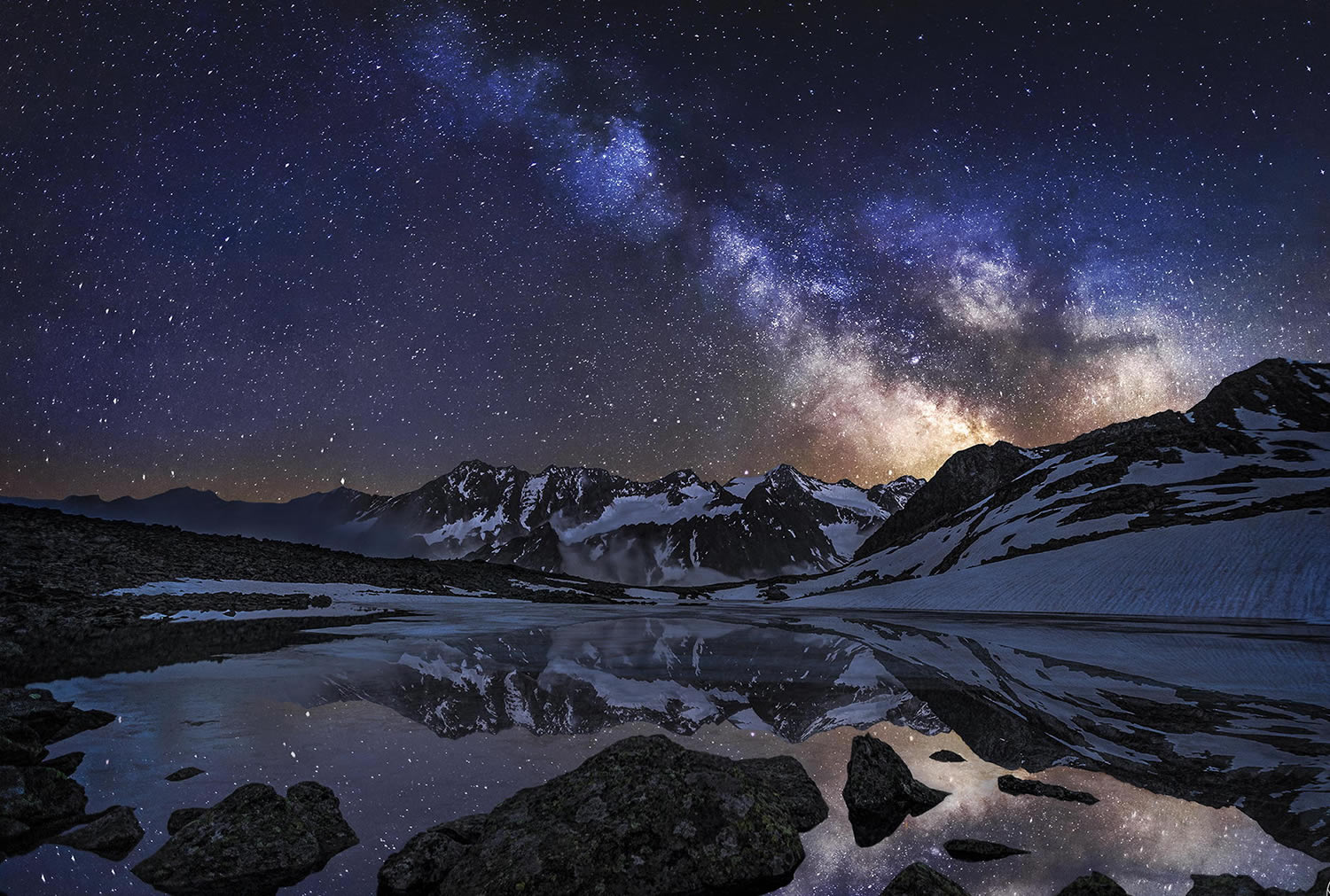 reflection photo of snowy mountains and milky way, by nicholas reommelt