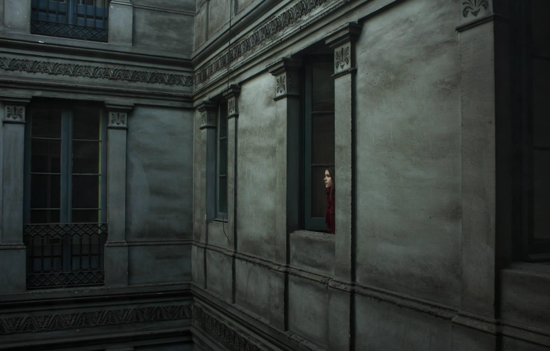 girl peeking from building window