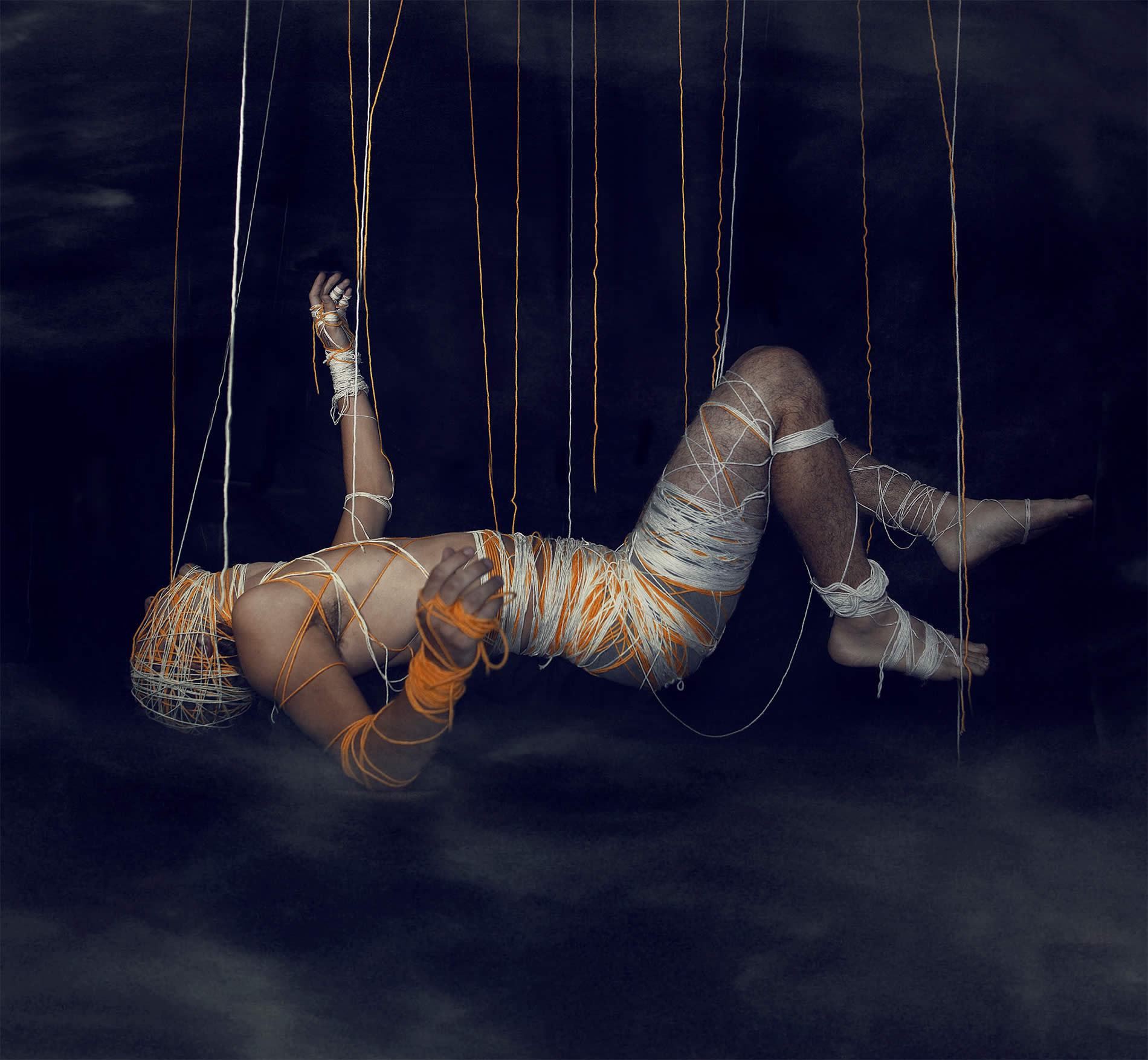 man hanging by strings, photo by kavan cardoza