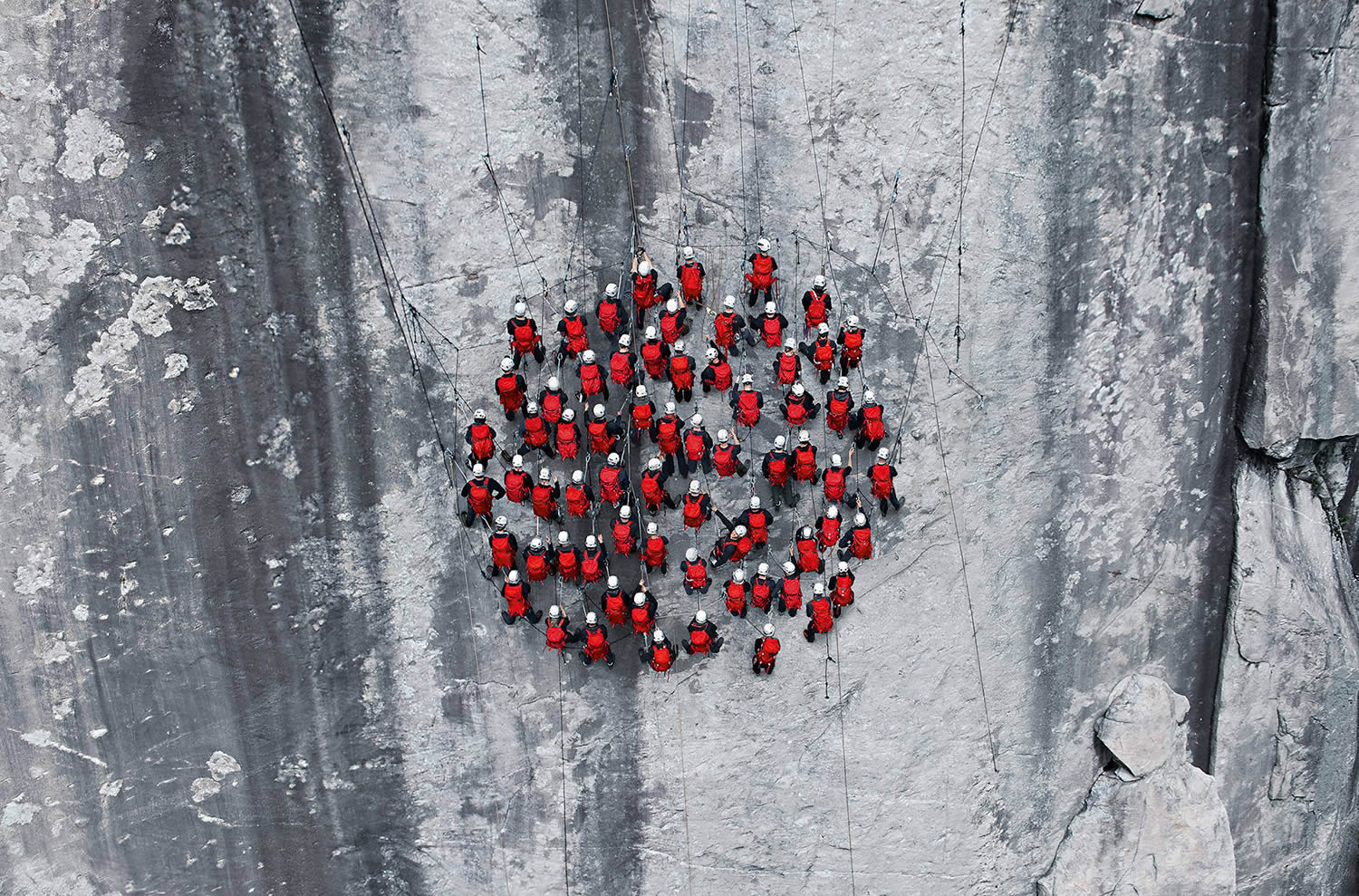 mountain climbers wearing red in a circle, photo by Robert Bösch mammut