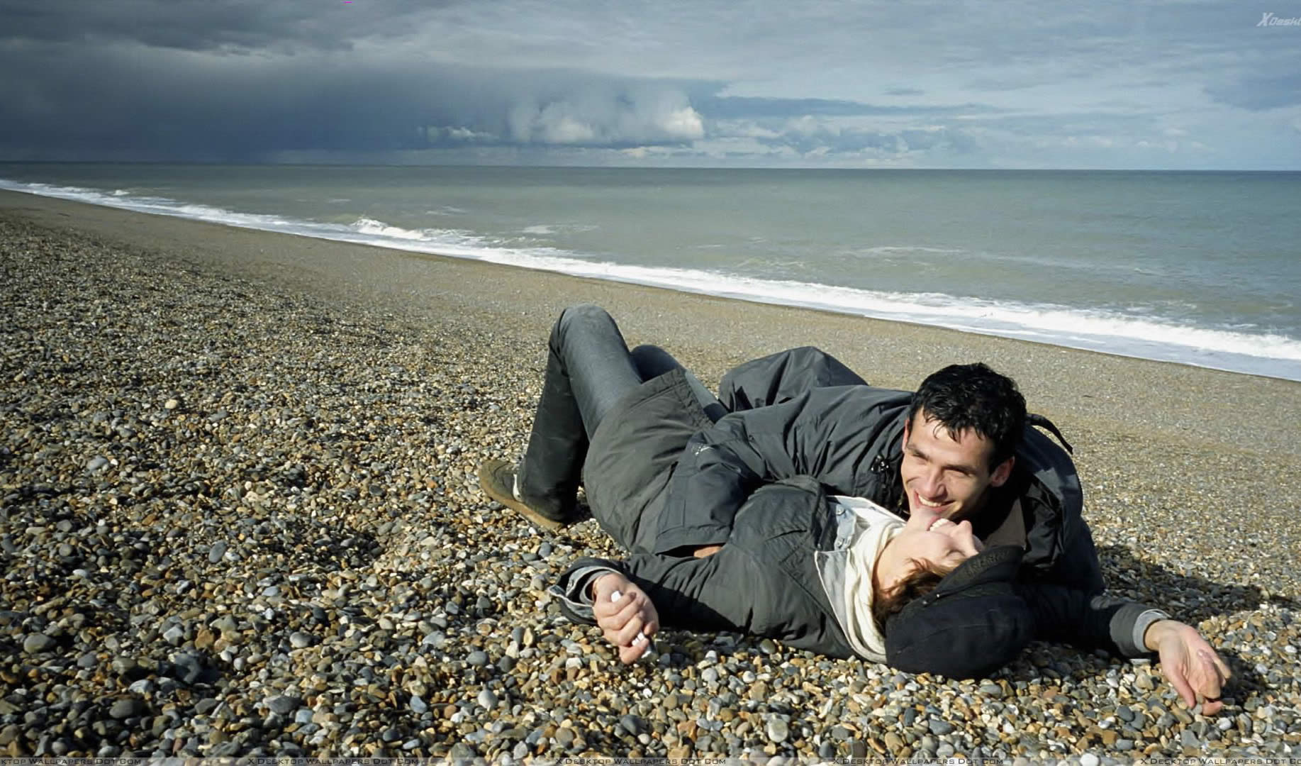 couple on the beach, lying down and hugging in 9 songs