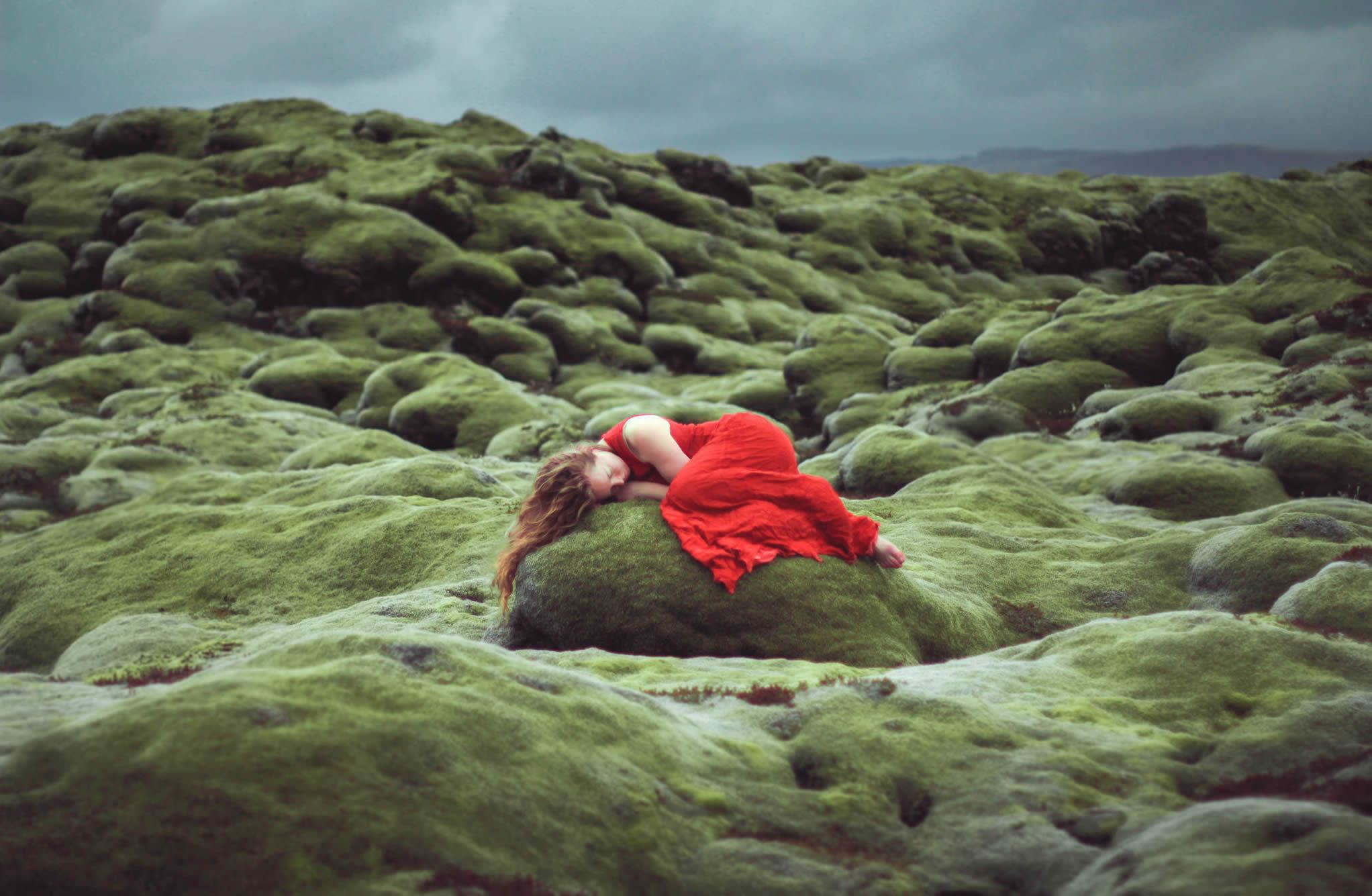 girl with red dress on rock, green landscape, photo by elizabeth gadd