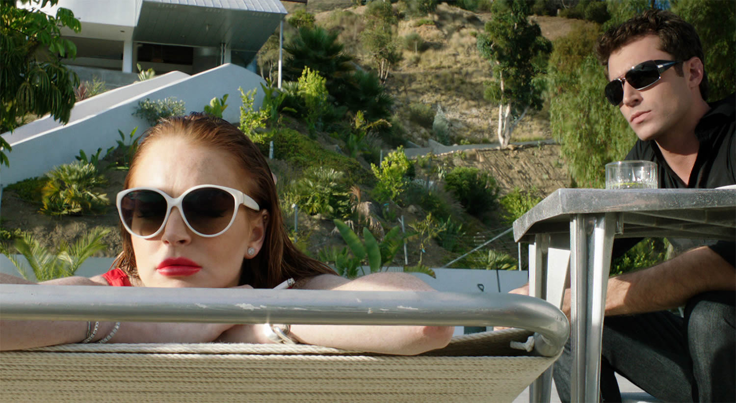 lindsay lohan in the canyons movie, lying and sunbathing