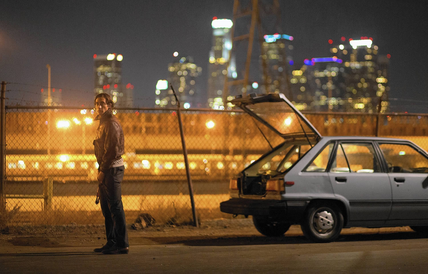 Jake Gyllenhaal beside a car with cityscape in back, nightcrawlers movie