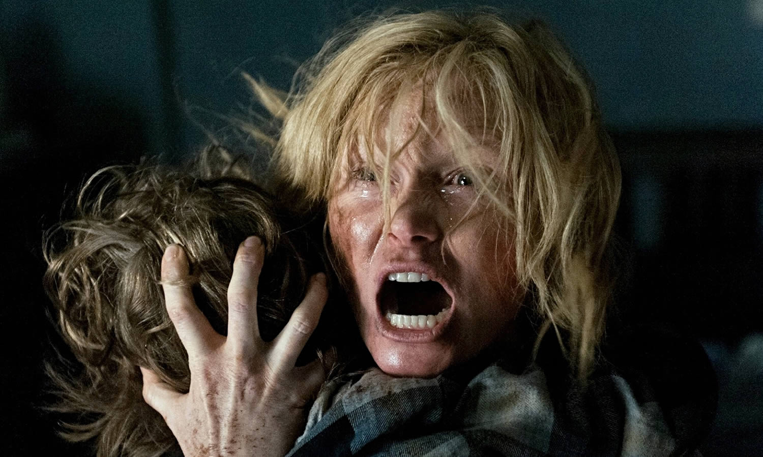 woman holding child and screaming in the babadook