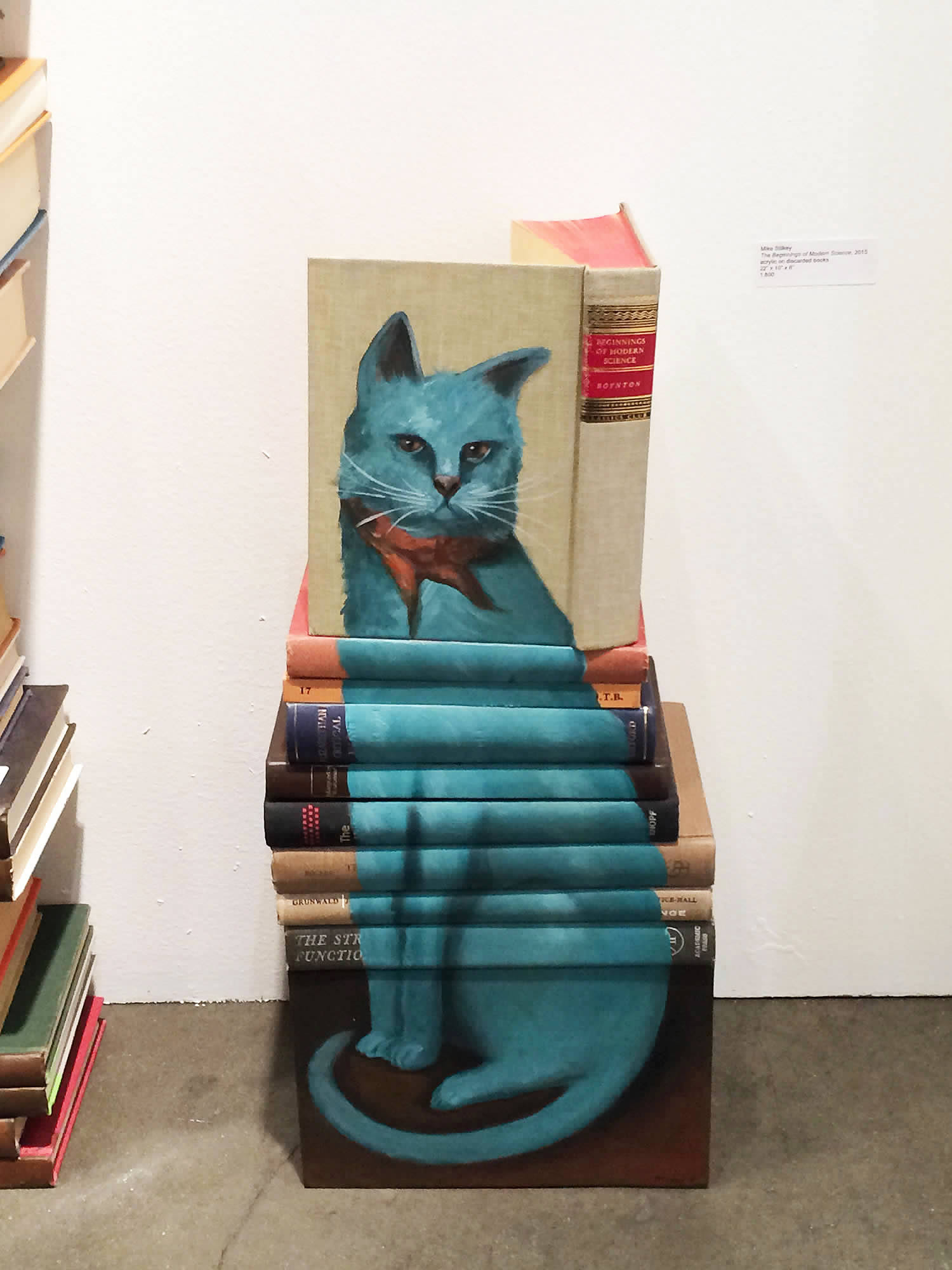 blue cat painted on book covers by mike stilkey