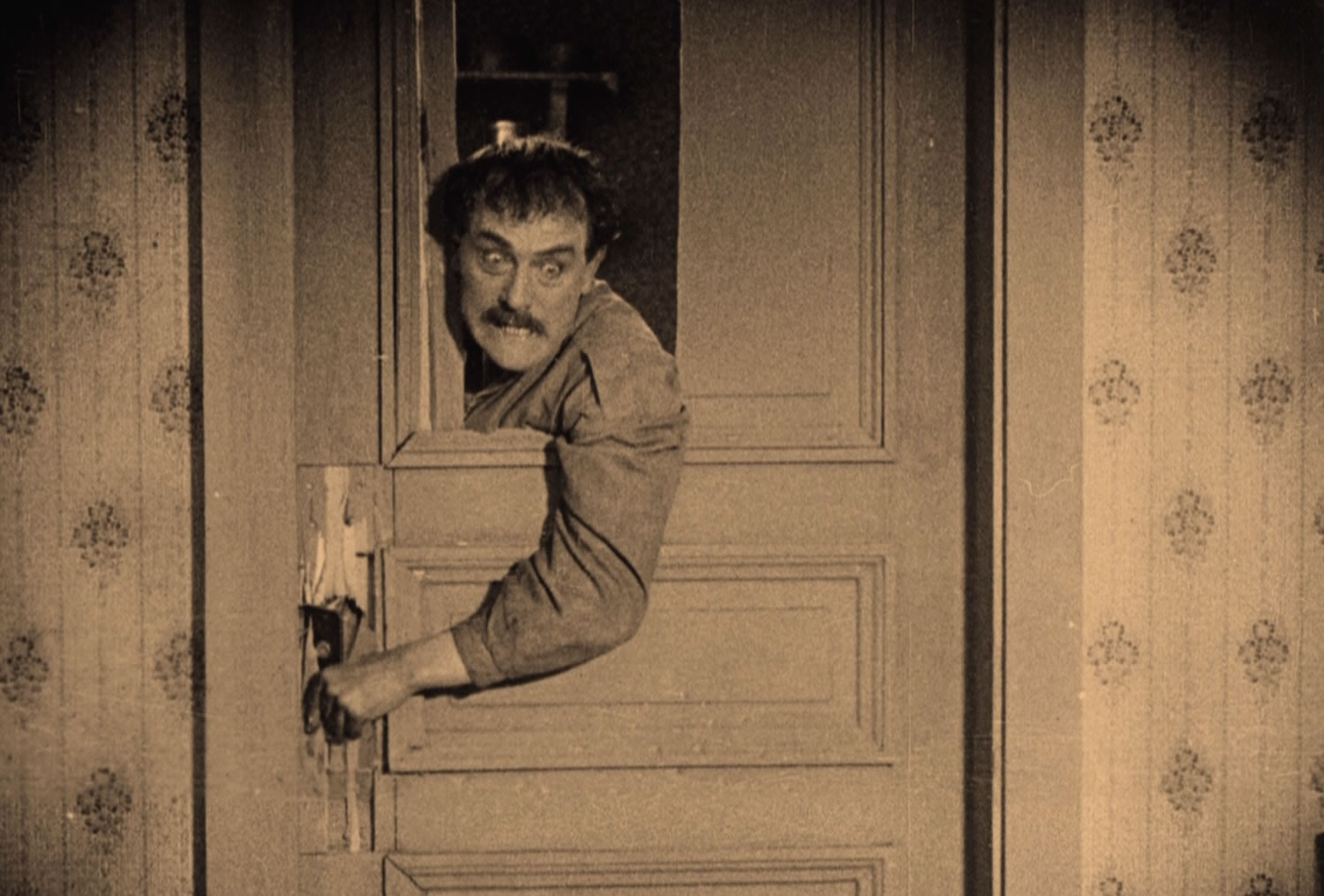 "David Holm (Victor Sjostrom) hacks at a wooden door in ""The Phantom Carriage"" (1921)"