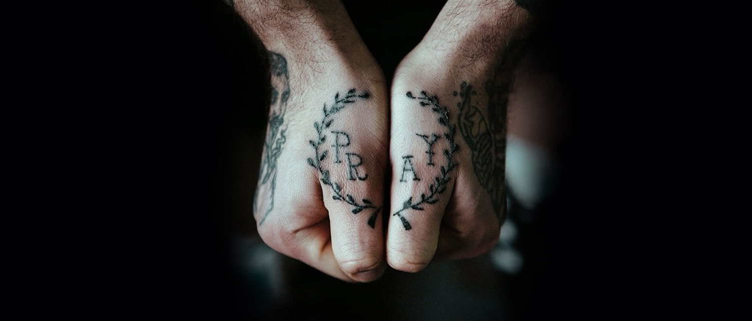 words pray tattooed on two hands
