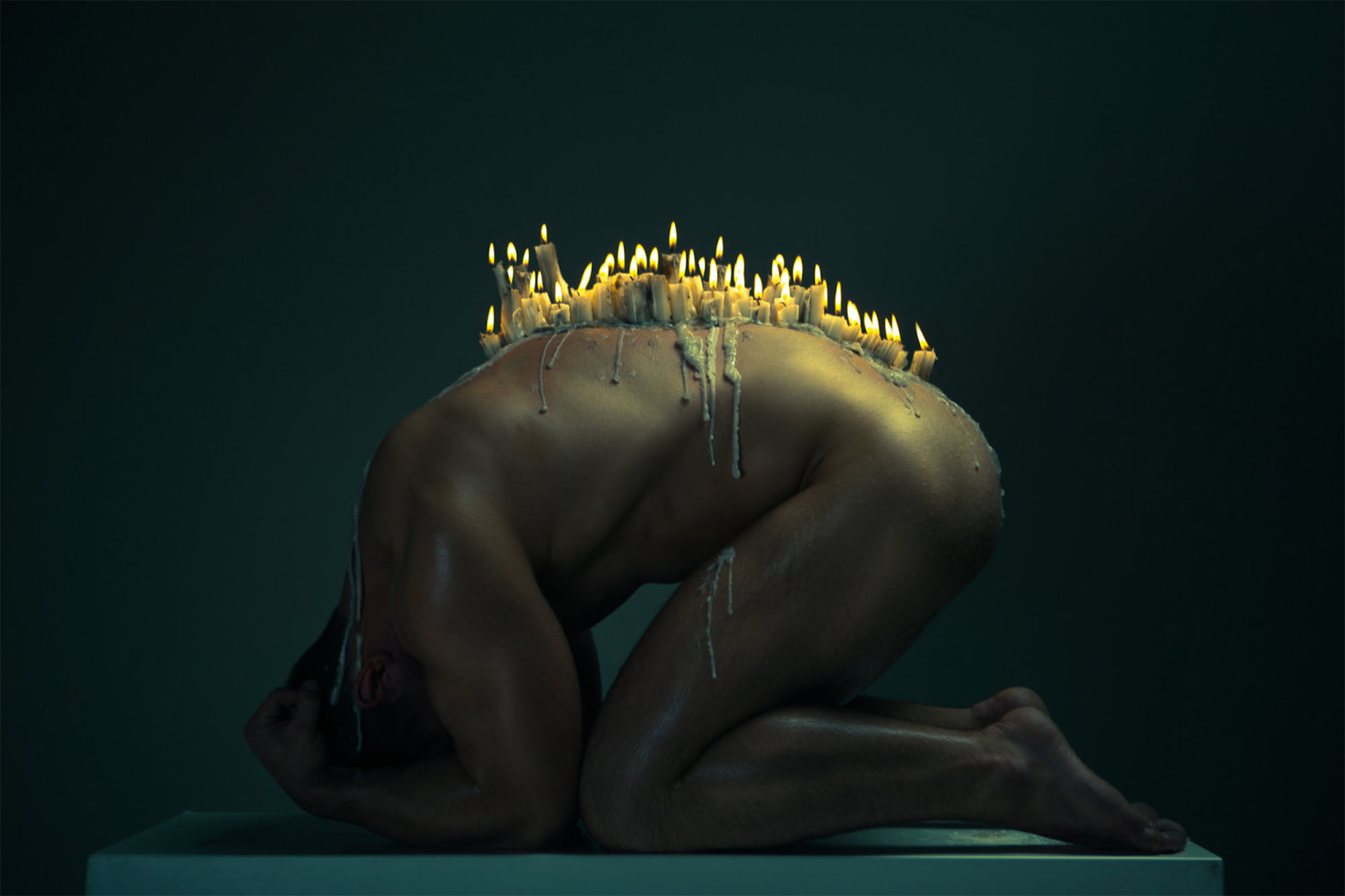 candles melting on man's back, nude photo by ekaterina zakharova