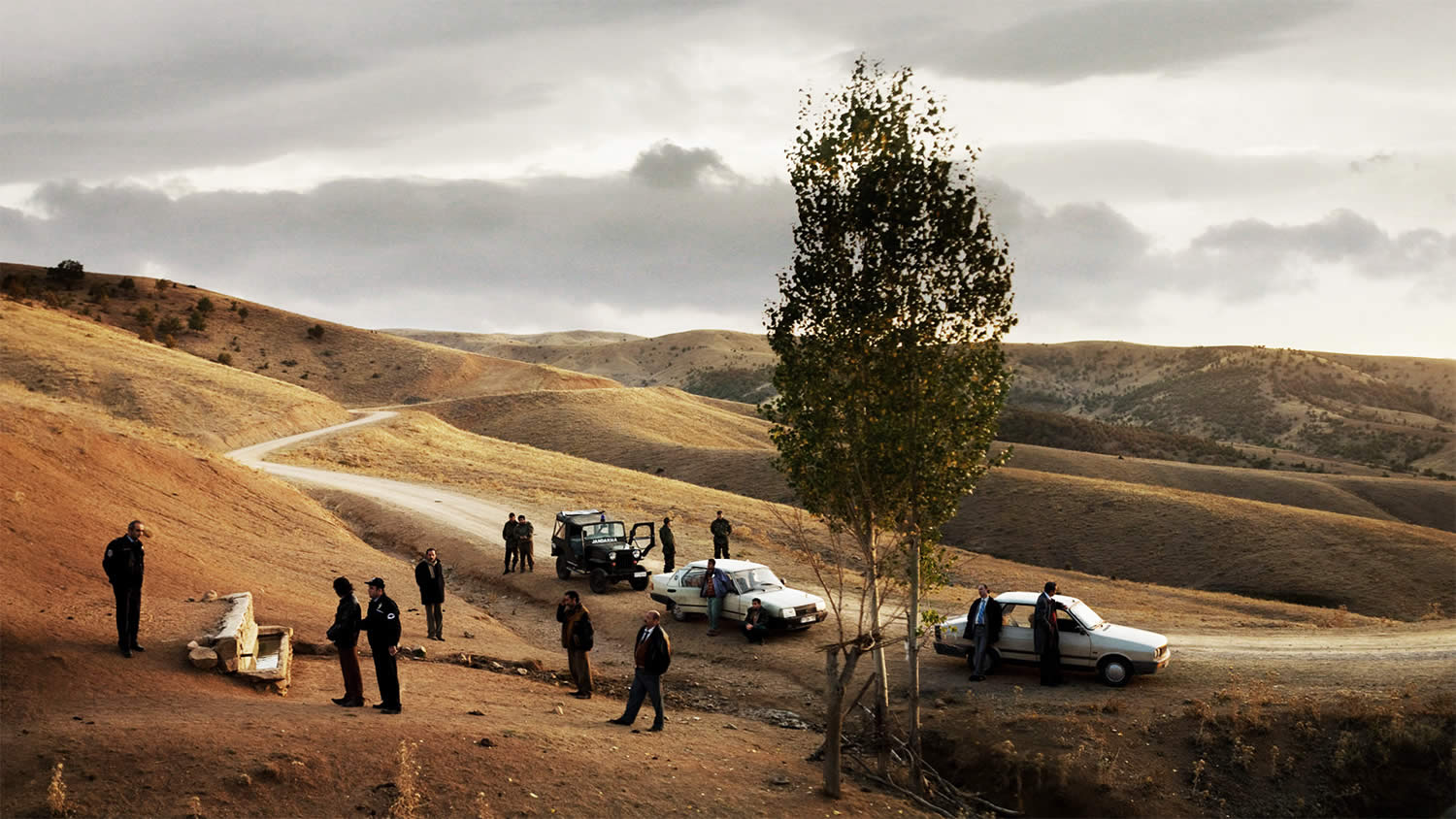 cars and men in field, in Once Upon a Time in Anatolia