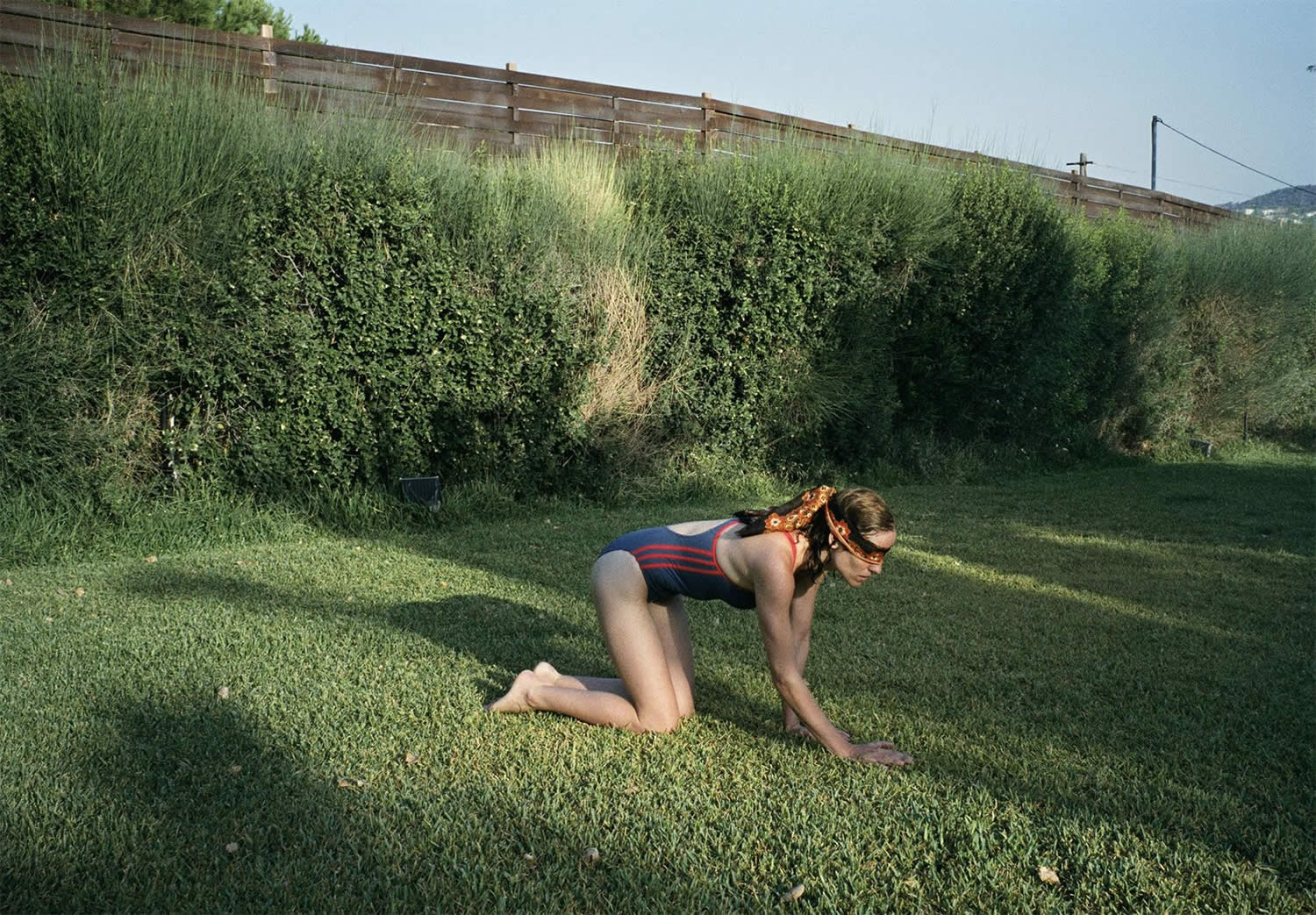 woman blindfolded crawling on grass in dogtooth movie