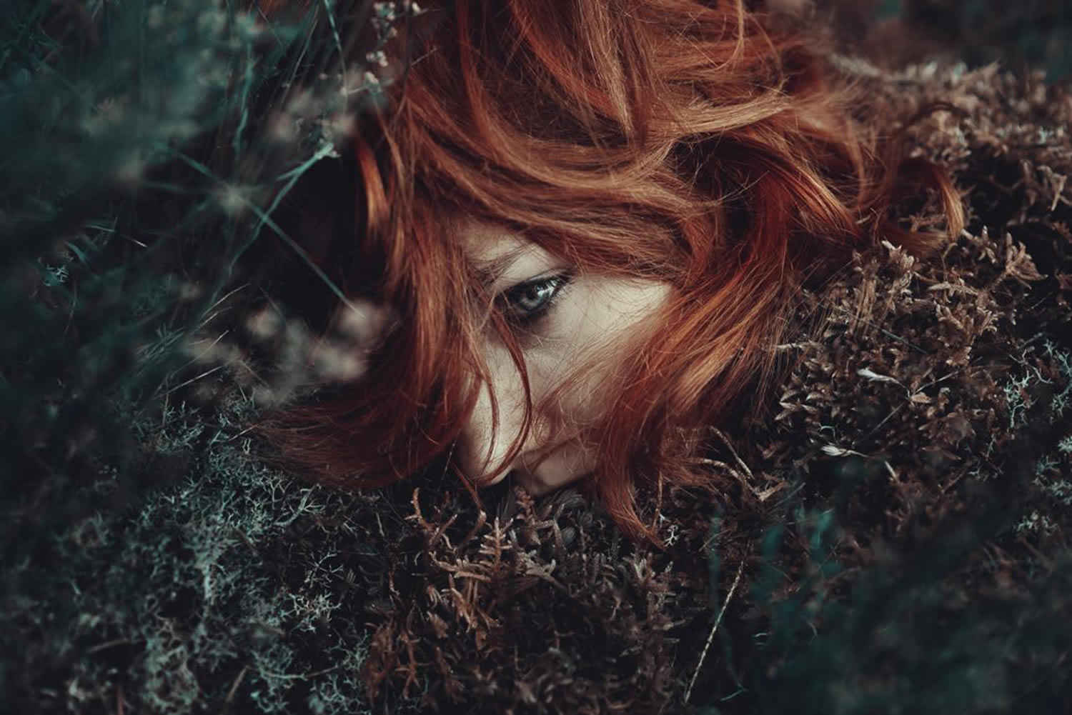 red hair woman lying in leaves