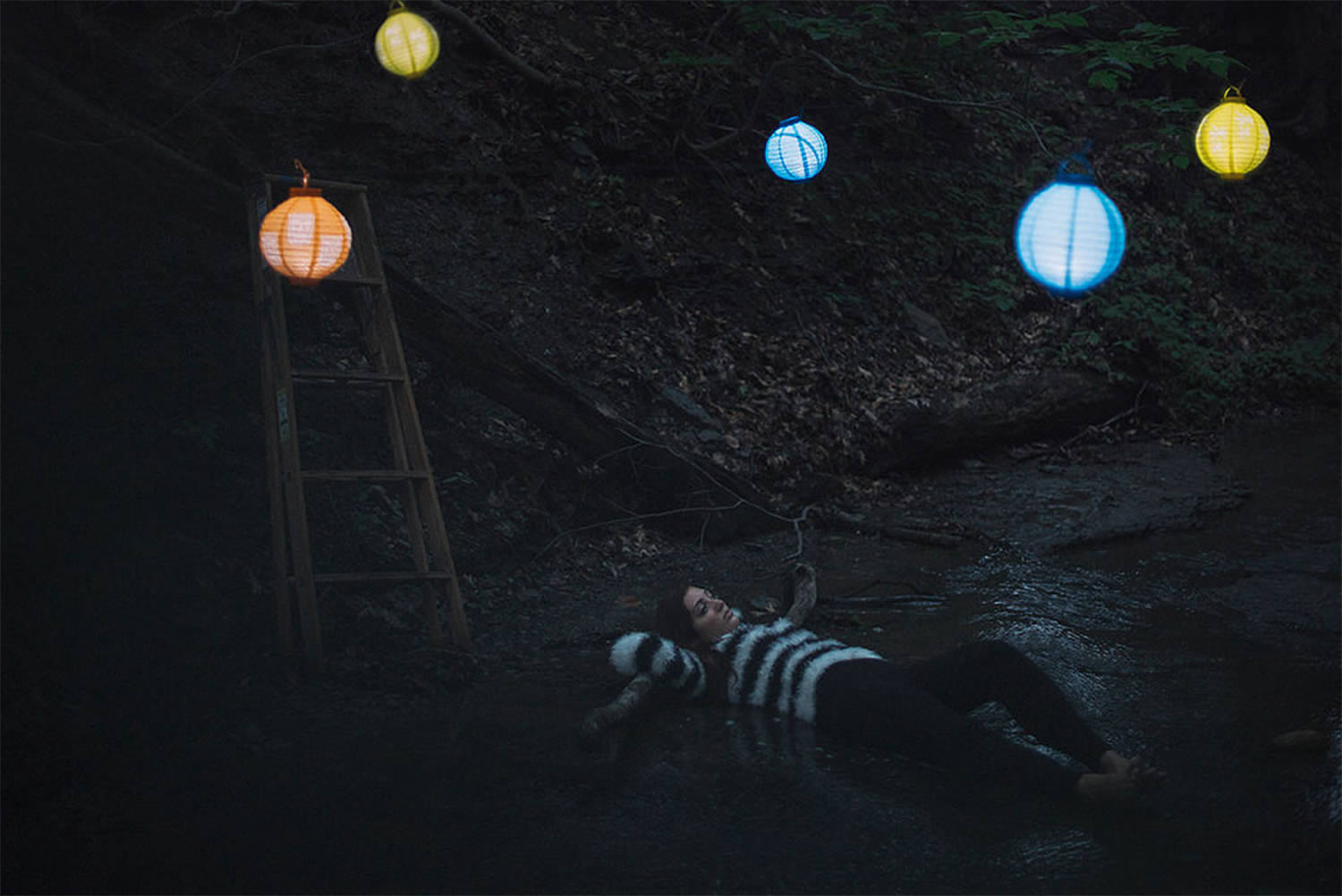 colored laterns in night sky. Girl laying down, alex currie