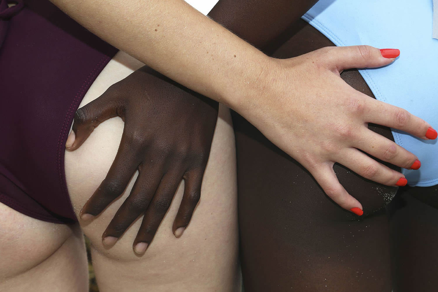 white and black. hands touching buttocks.