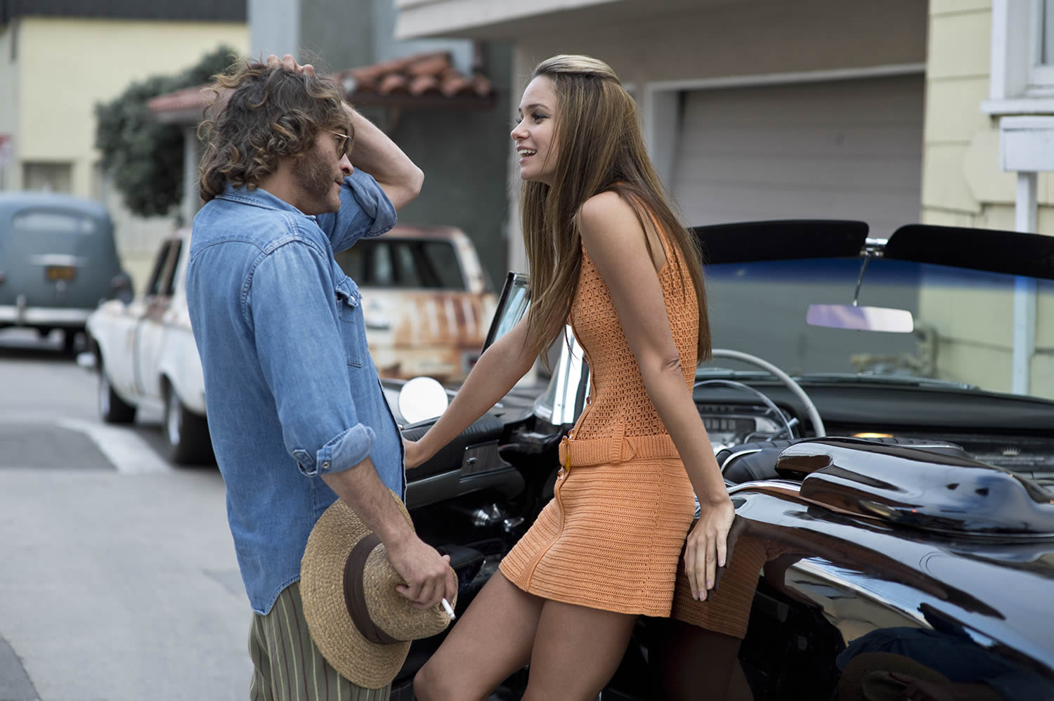 joaquim phoenix talking to girl on street in inherent vice
