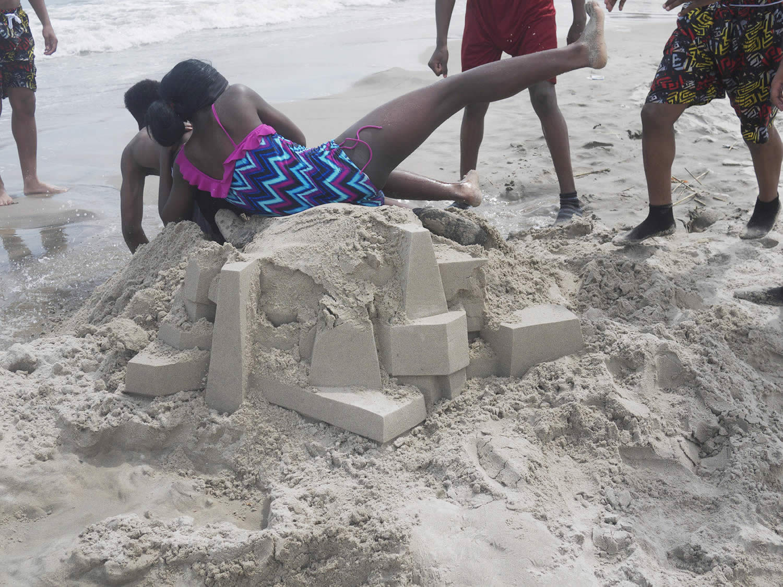 kids falling over sand castle