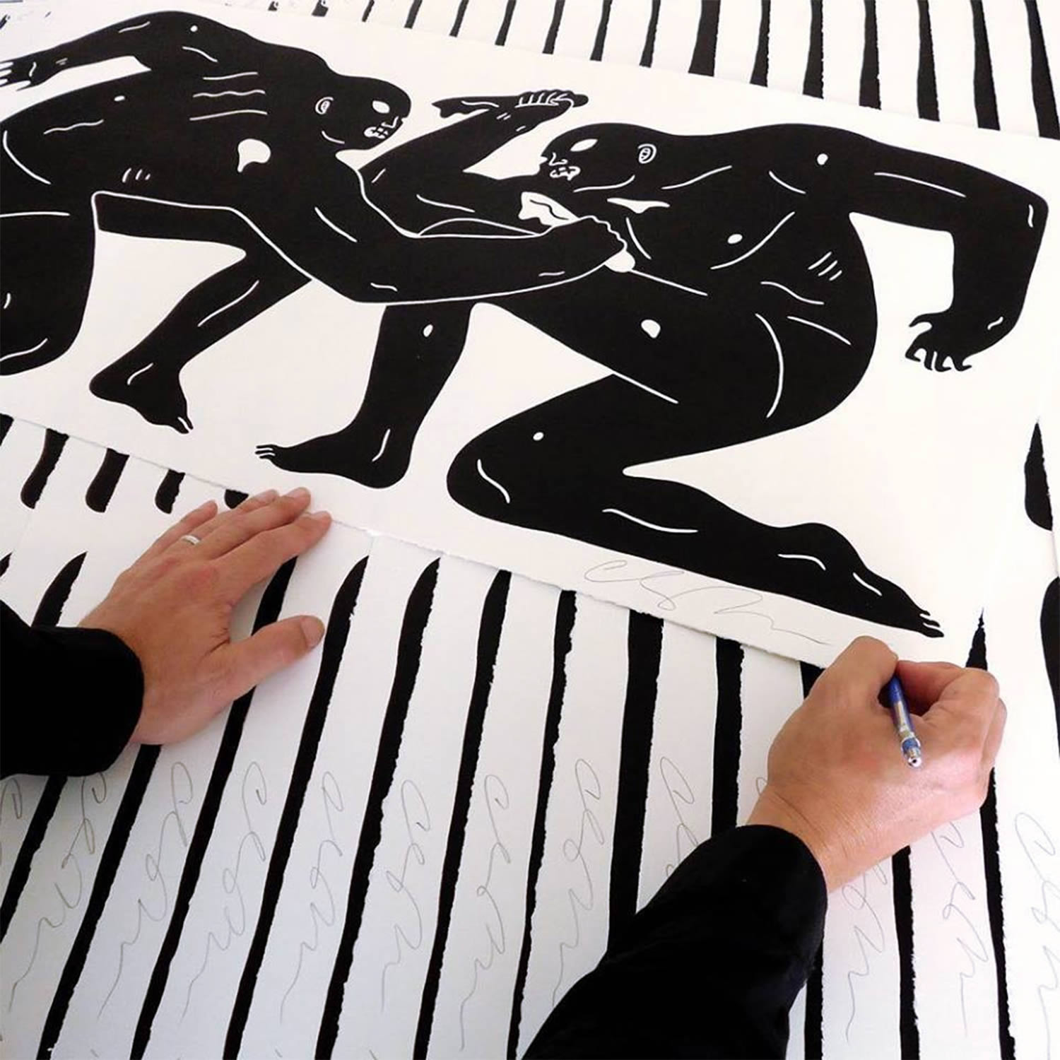 the artist signing a print, cleon peterson