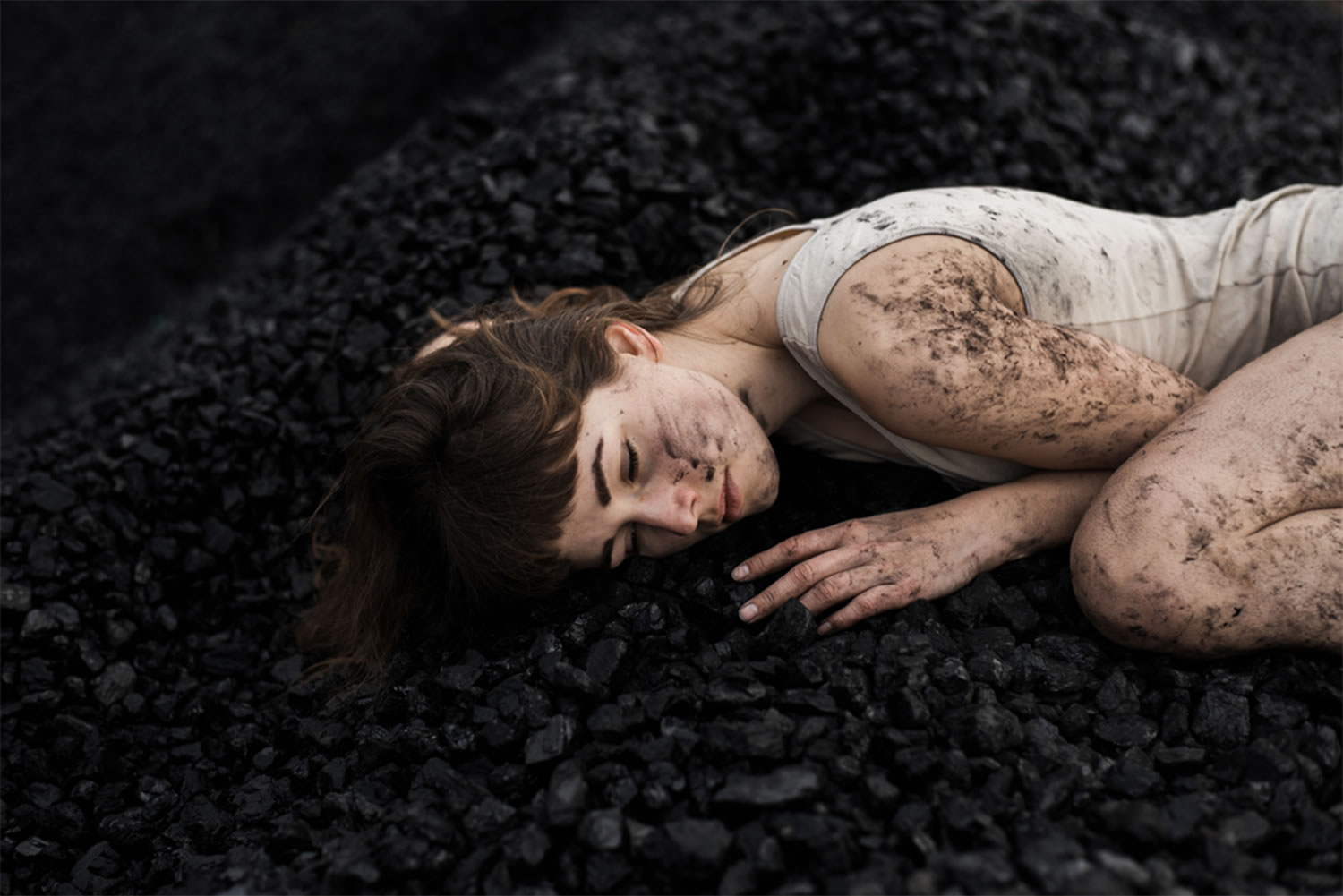 girl laying over coal, all dirty