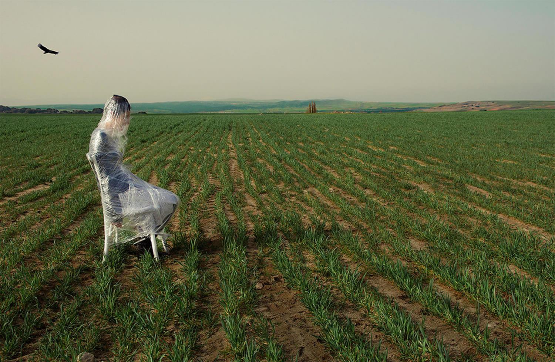 girl in plastic wrap, sitting in field
