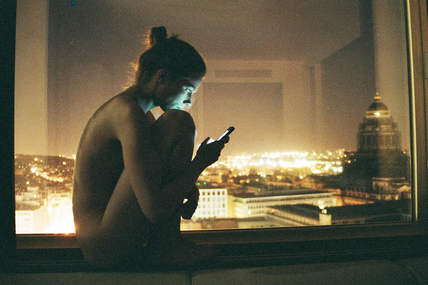 woman on windowsill, iphone