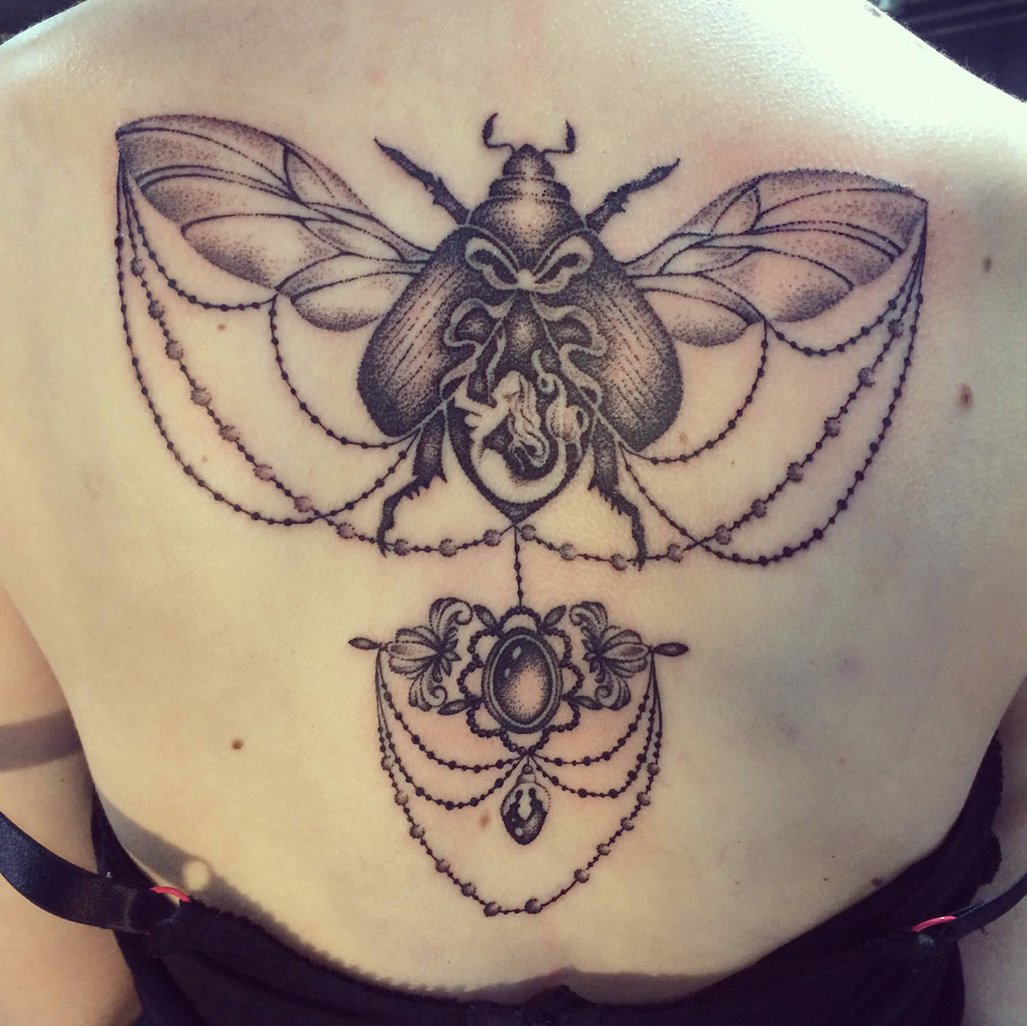 insect and victorian jewelry tattoo on back