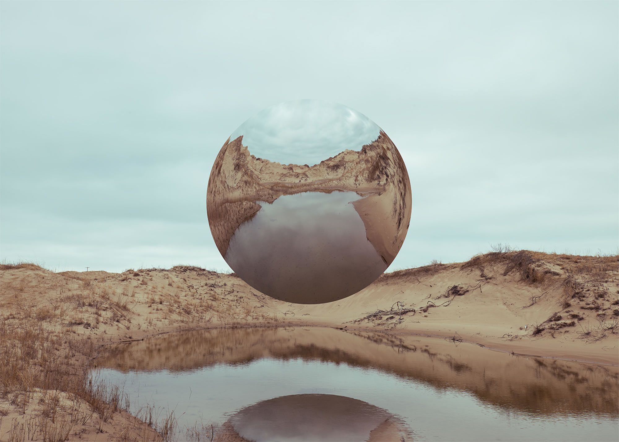 vicissitudes by logan zillmer, circular mirror above beach land